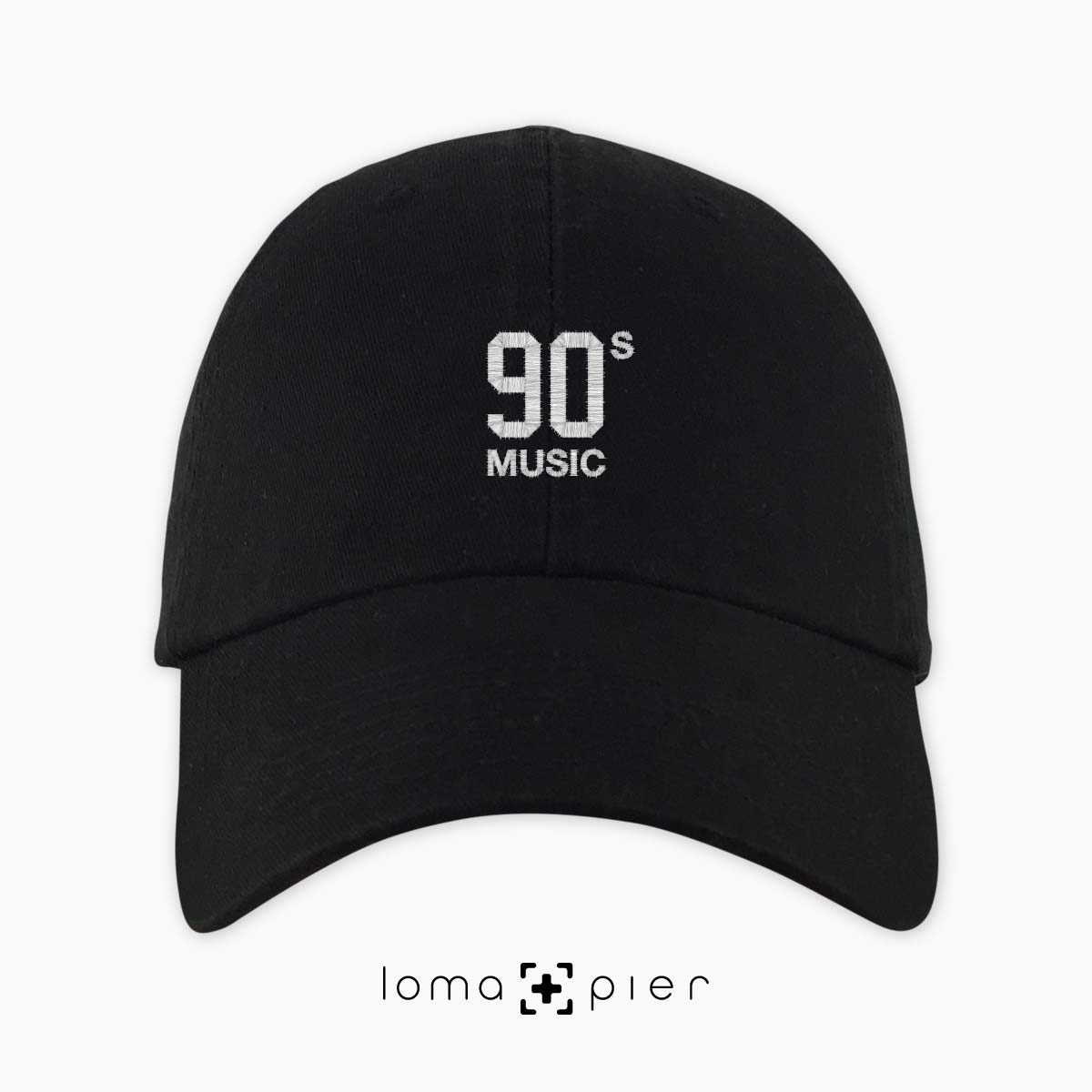 90's MUSIC typography embroidered on a black unstructured dad hat with white thread by loma+pier hat store made in the USA