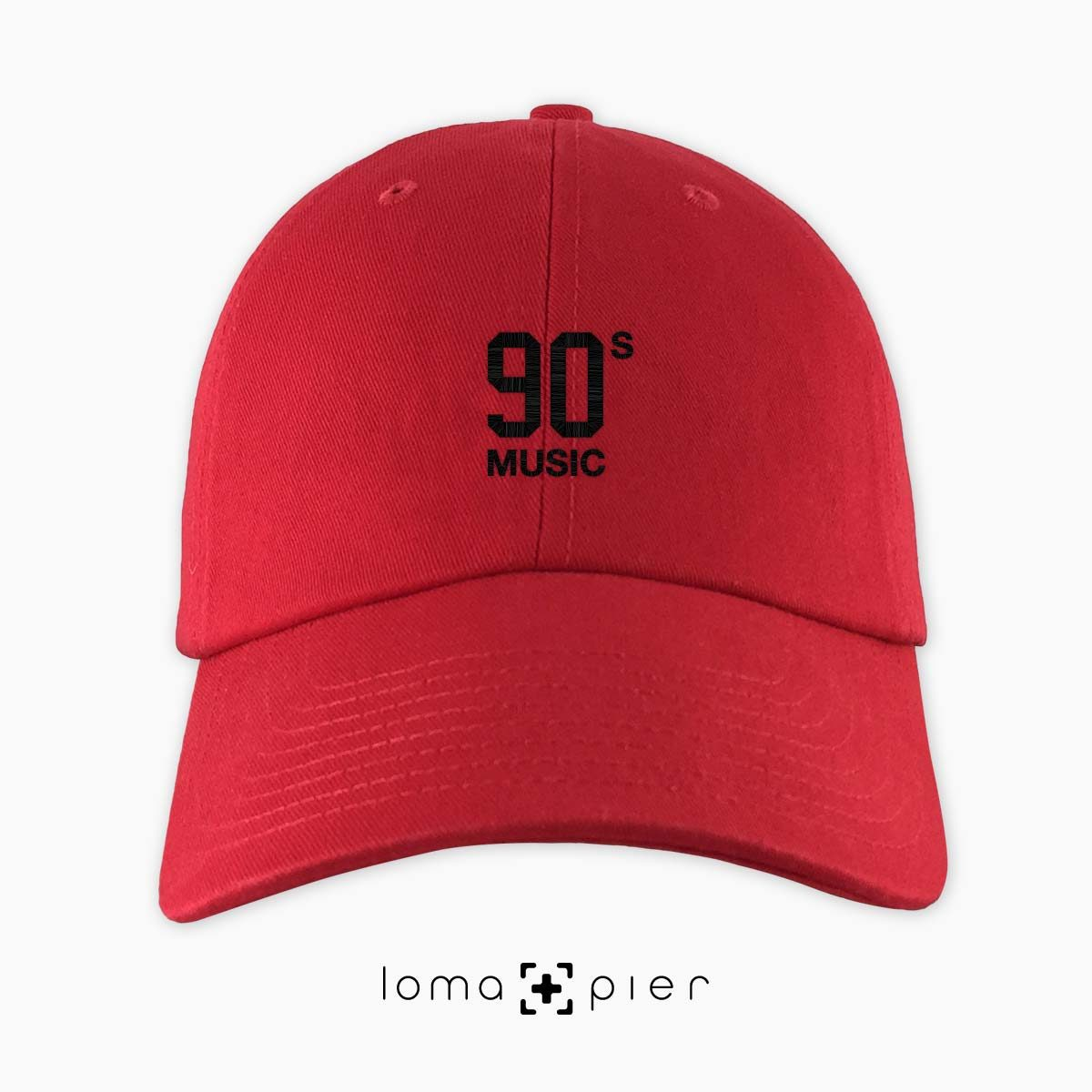 90's MUSIC typography embroidered on a red unstructured dad hat with black thread by loma+pier hat store made in the USA