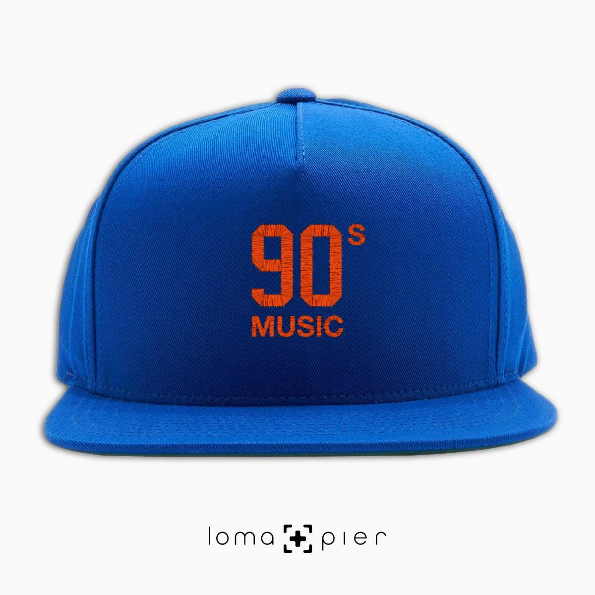 90's MUSIC typography embroidered on a royal blue classic snapback hat with orange thread by loma+pier hat store