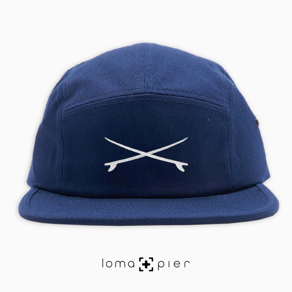 X MARKS THE SPOT icon embroidered on a navy blue cotton 5-panel hat by loma+pier hat store