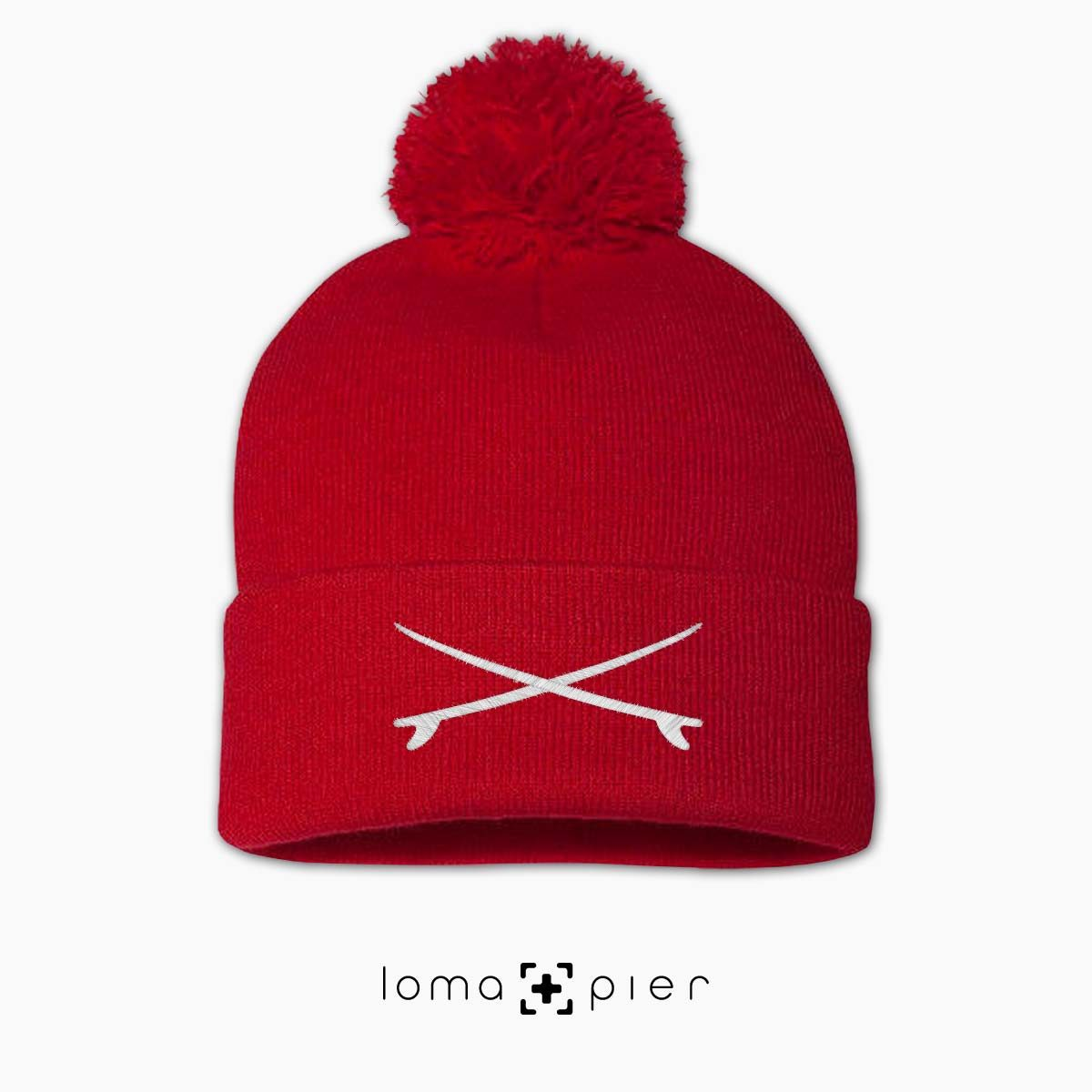 X MARKS THE SURF icon embroidered on a red pom pom beanie by loma+pier beanie store