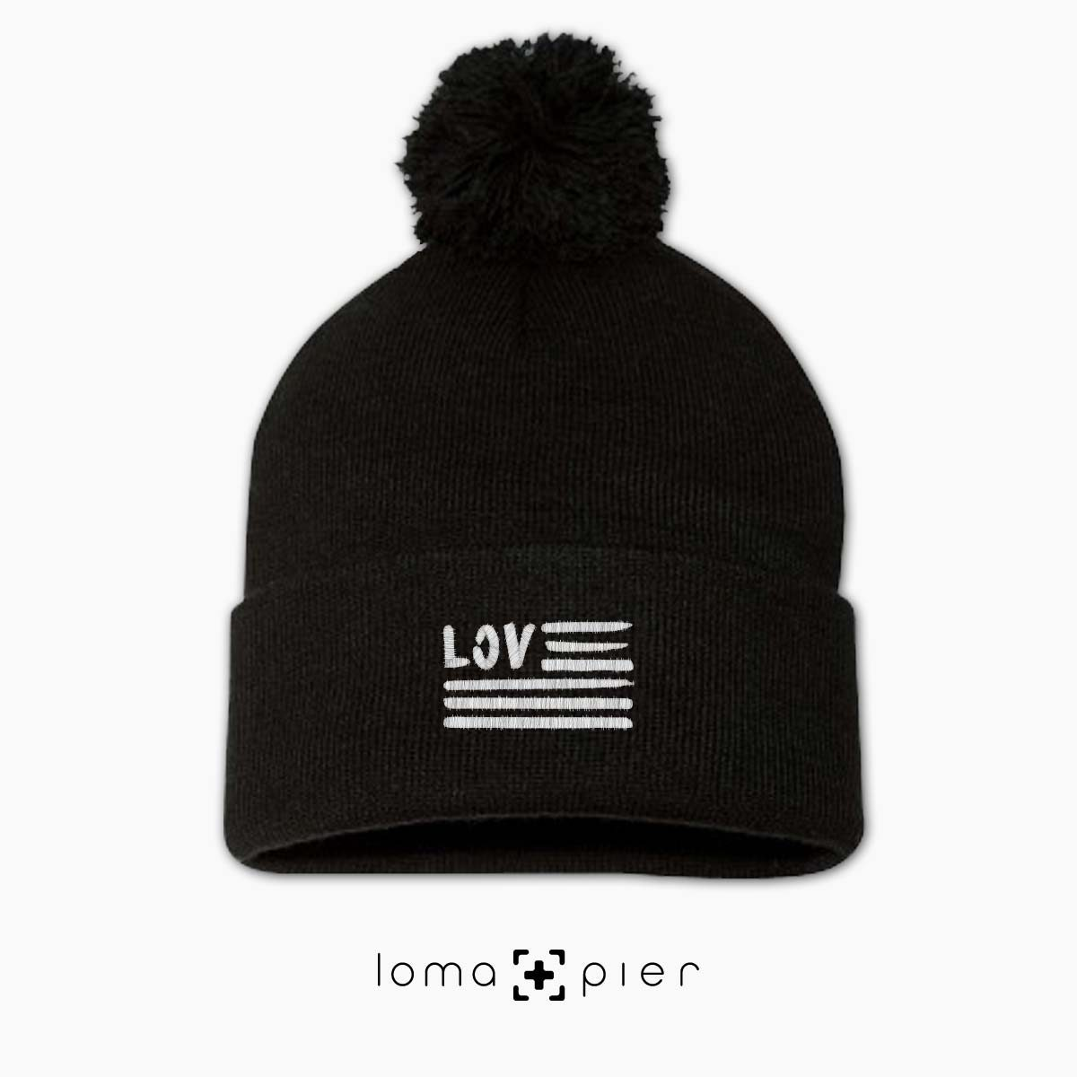 AMERICAN LOVE icon embroidered on a black pom pom beanie with white thread by loma+pier hat store