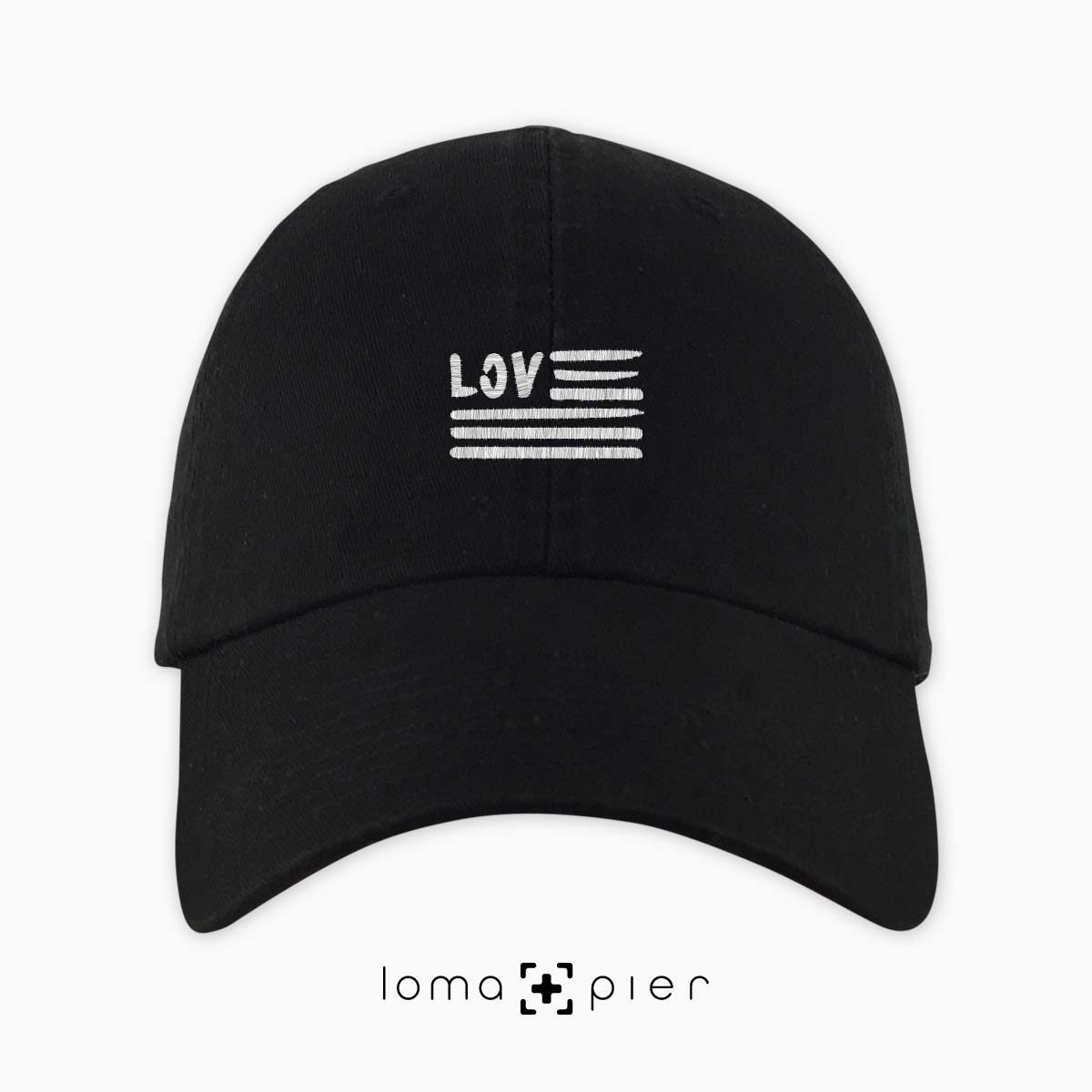 AMERICAN LOVE icon embroidered on a black unstructured dad hat with white thread by loma+pier hat store made in the USA