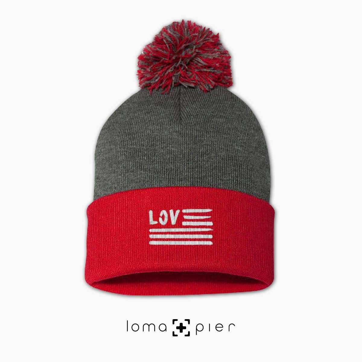 AMERICAN LOVE icon embroidered on a heather grey and red pom pom beanie with white thread by loma+pier hat store