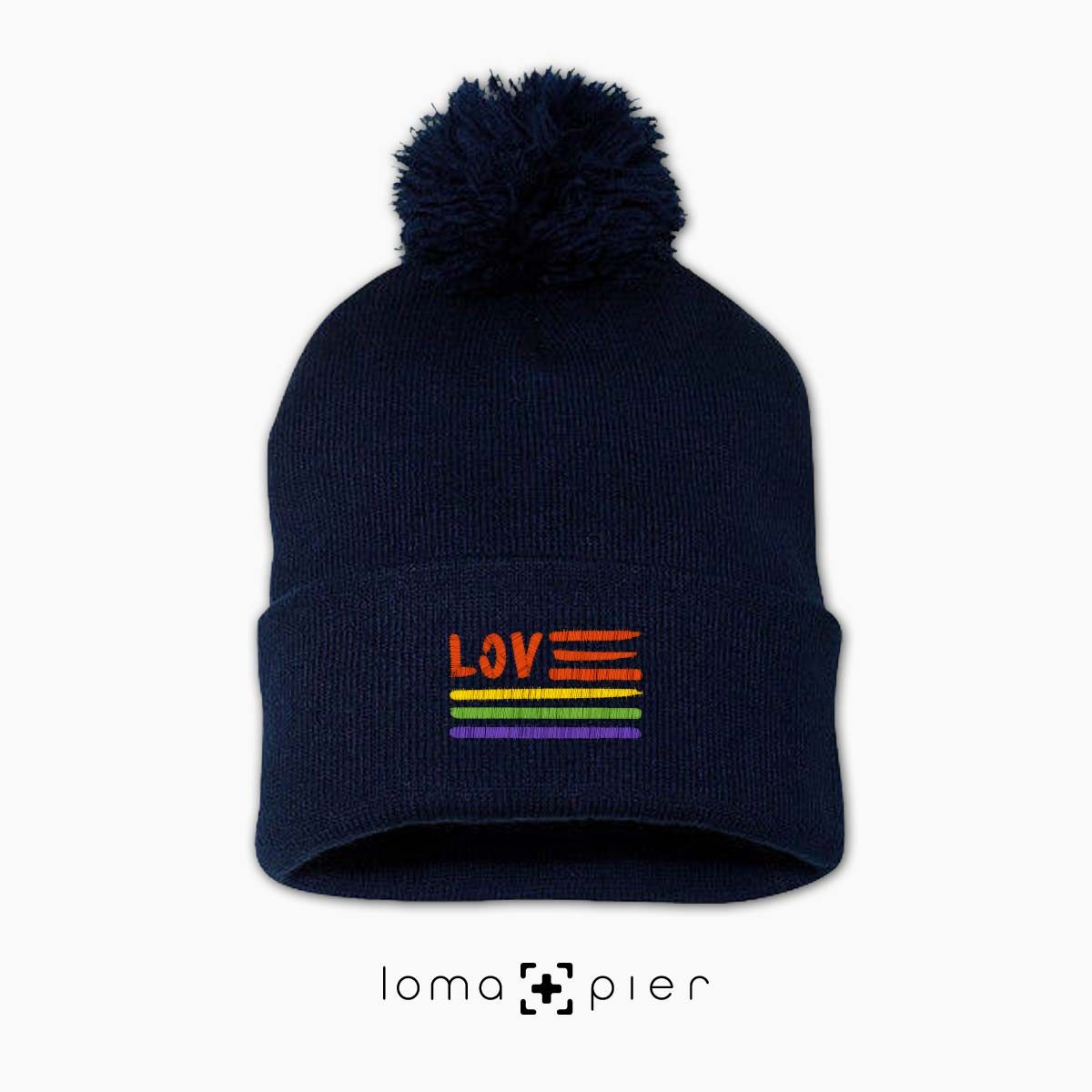 AMERICAN LOVE ​GAY PRIDE icon embroidered on a navy blue pom pom beanie with multicolor thread by loma+pier hat store