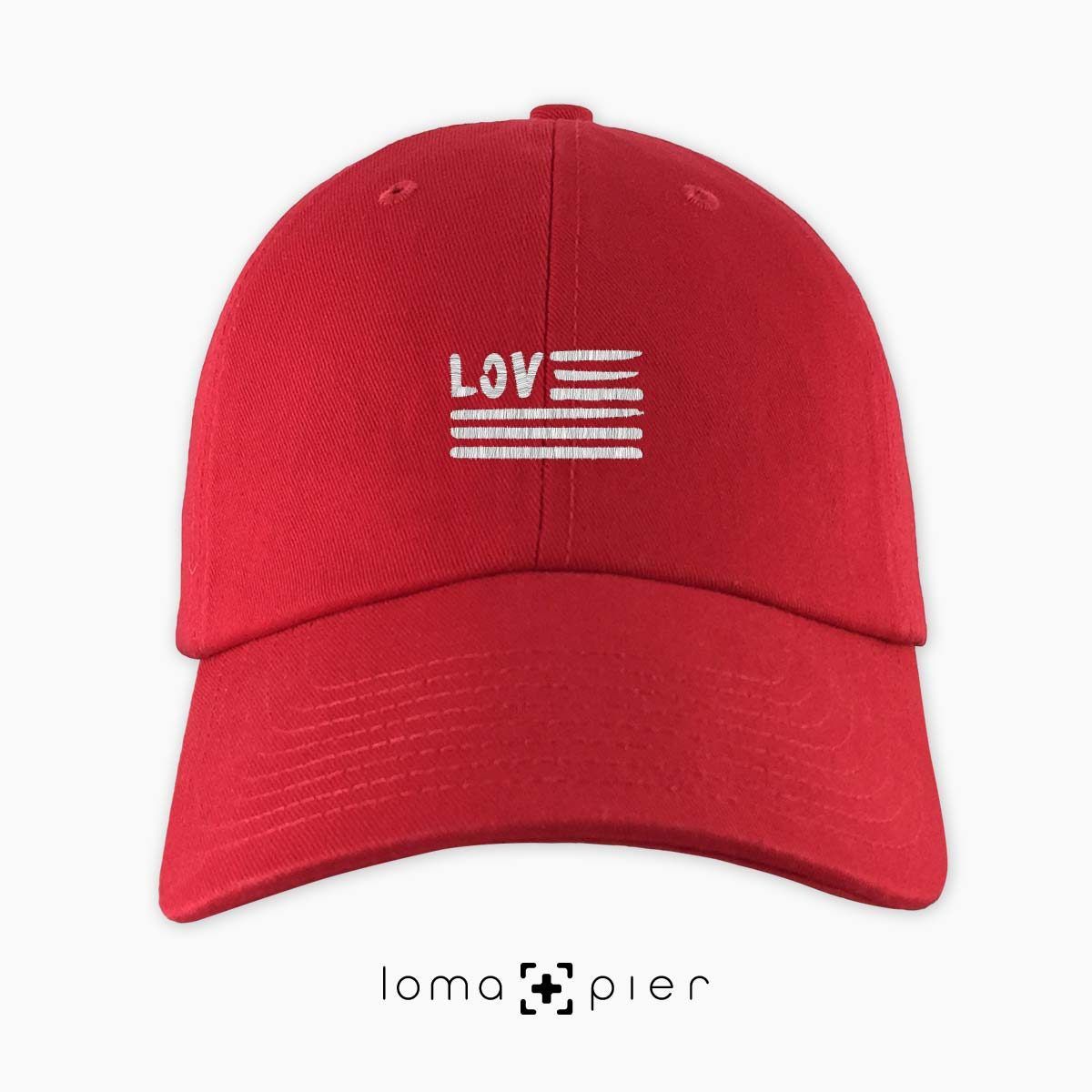 AMERICAN LOVE icon embroidered on a red unstructured dad hat with white thread by loma+pier hat store made in the USA