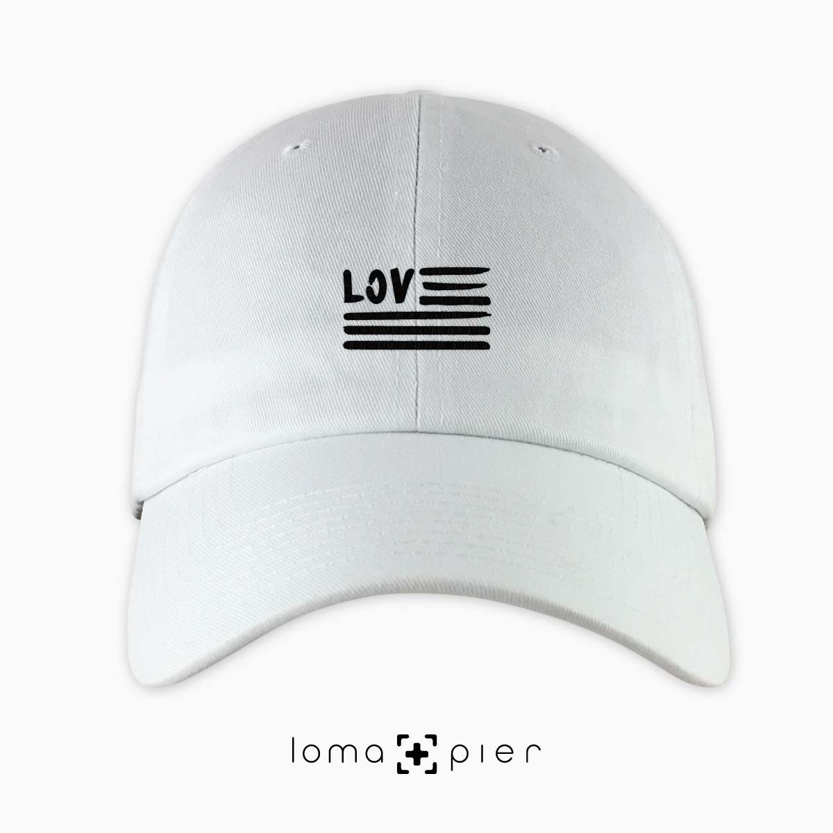 AMERICAN LOVE icon embroidered on a white unstructured dad hat with black thread by loma+pier hat store made in the USA