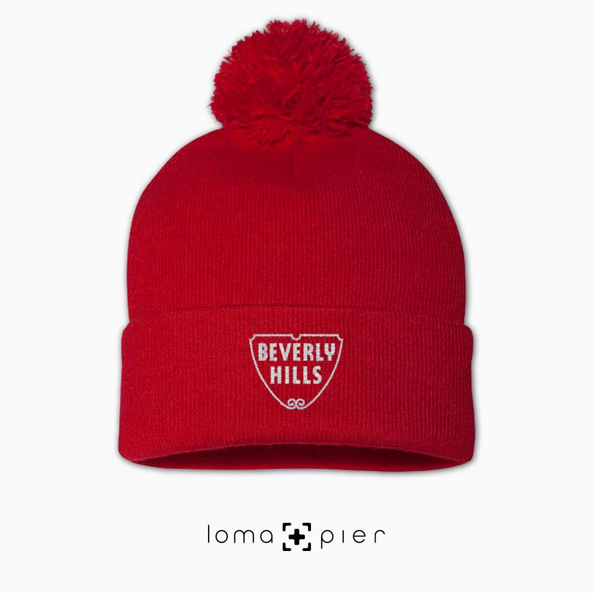 BEVERLY HILLS typography embroidered on a red pom pom beanie with white thread by loma+pier hat store