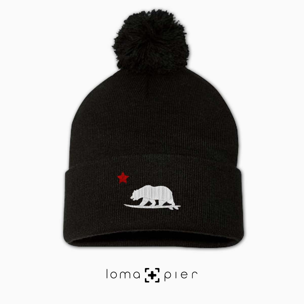 CALIFORNIA BEAR SURFING icon embroidered on a black pom pom beanie with white and red thread by loma+pier hat store
