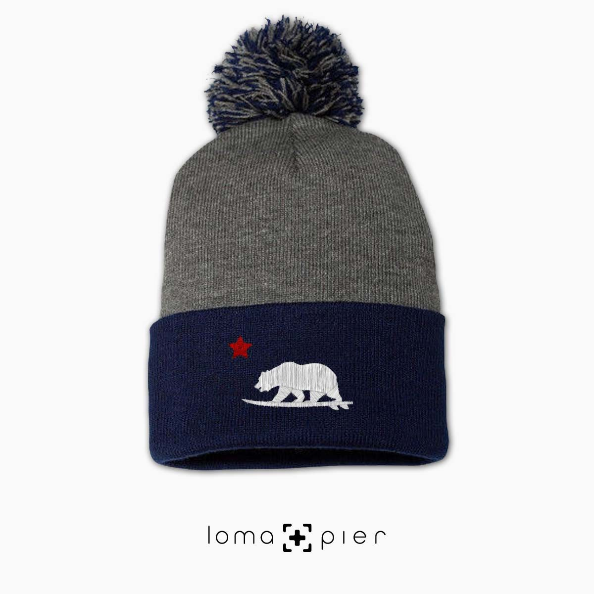 CALIFORNIA BEAR SURFING icon embroidered on a heather grey and navy blue pom pom beanie with white and red thread by loma+pier hat store