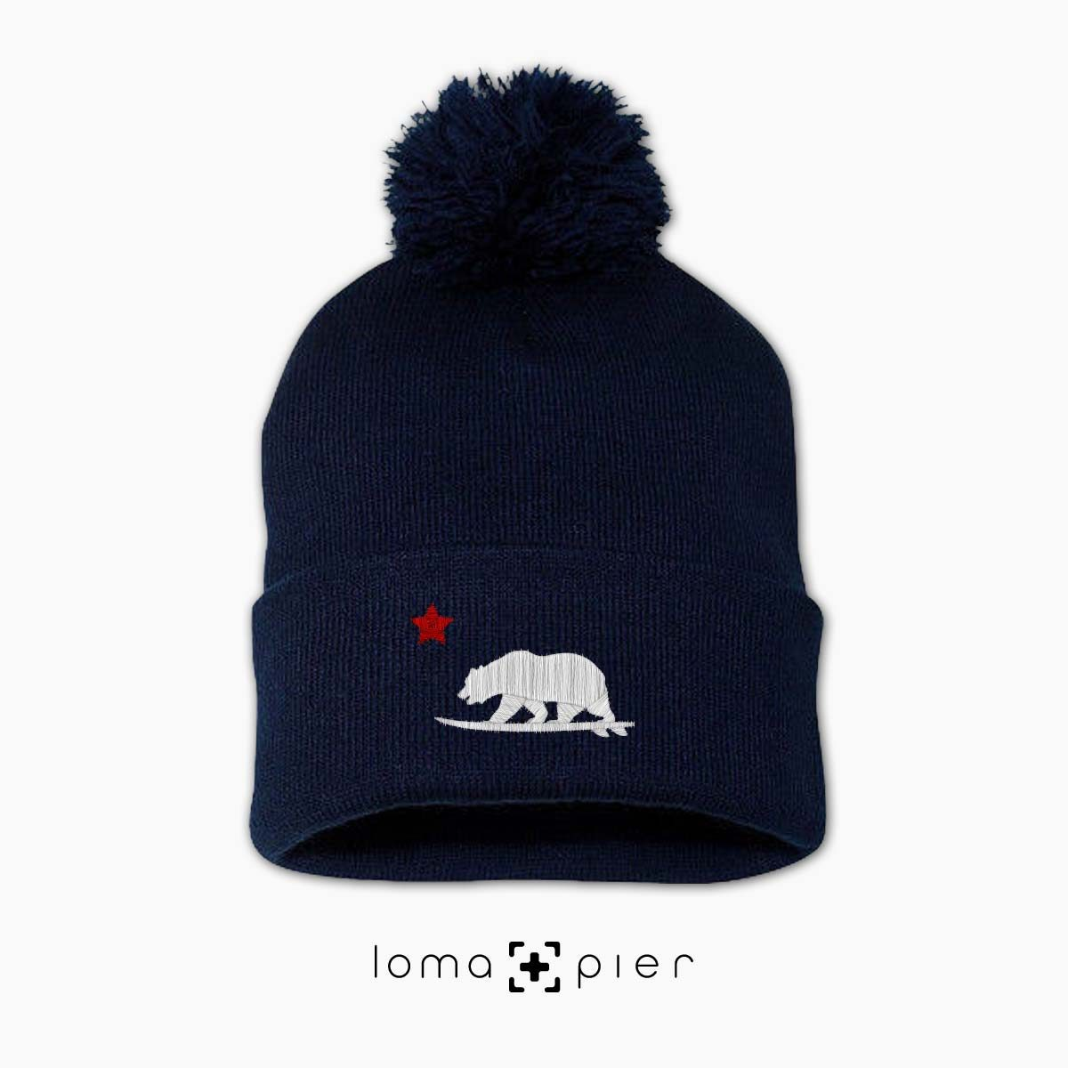 CALIFORNIA BEAR SURFING icon embroidered on a navy blue pom pom beanie with white and red thread by loma+pier hat store