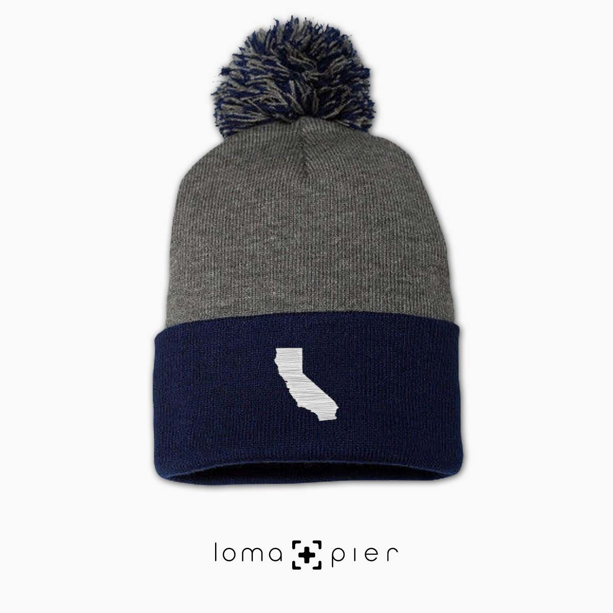 CALIFORNIA silhouette icon embroidered on a grey navy pom pom beanie by loma+pier hat store