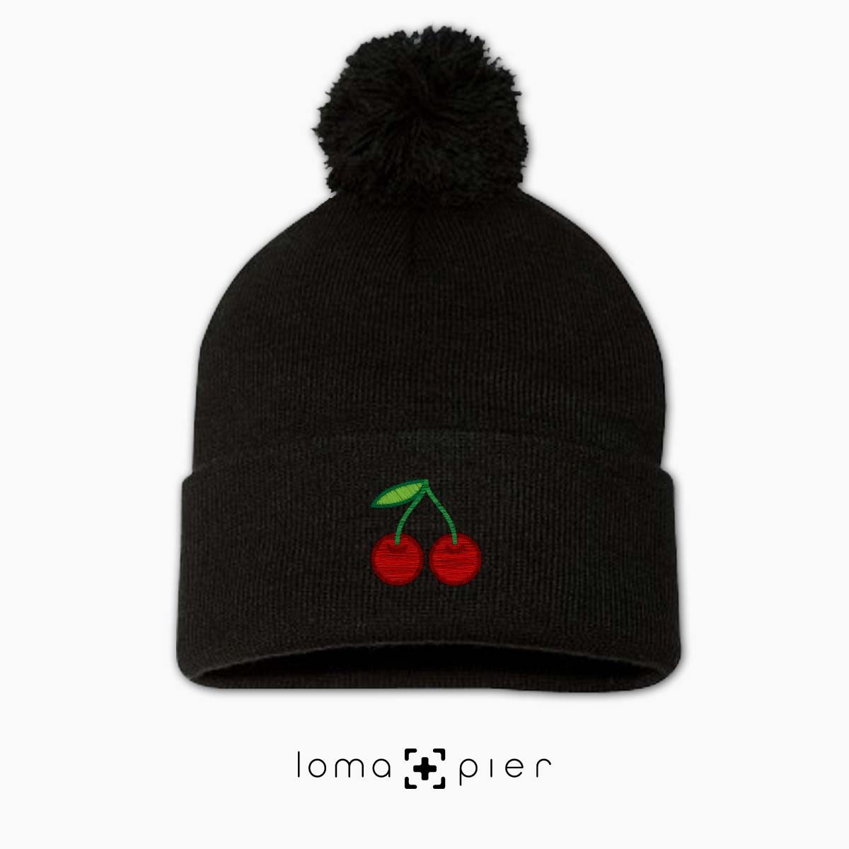 CHERRIES icon embroidered on a black pom pom beanie by loma+pier beanie store