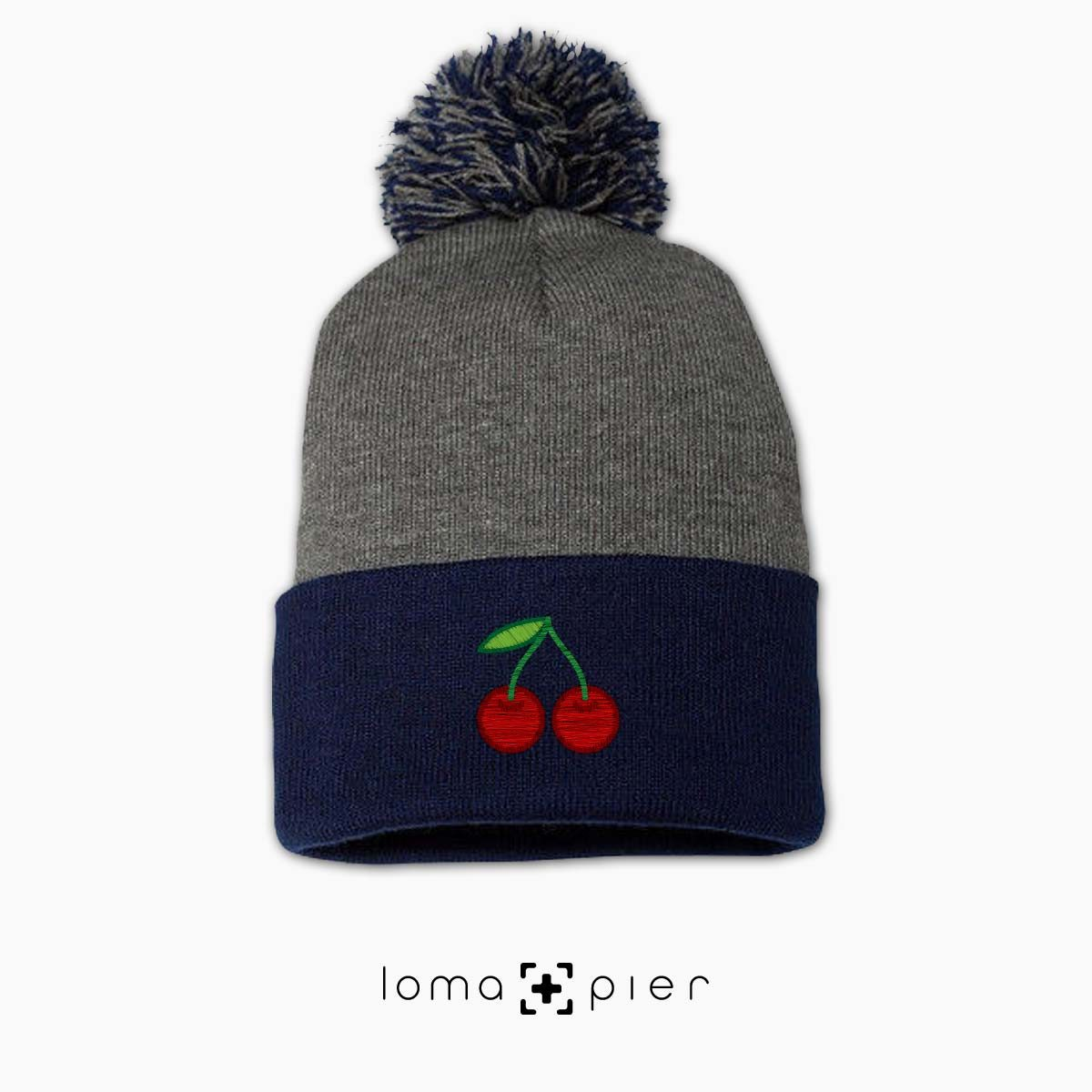 CHERRIES icon embroidered on a grey navy pom pom beanie by loma+pier beanie store