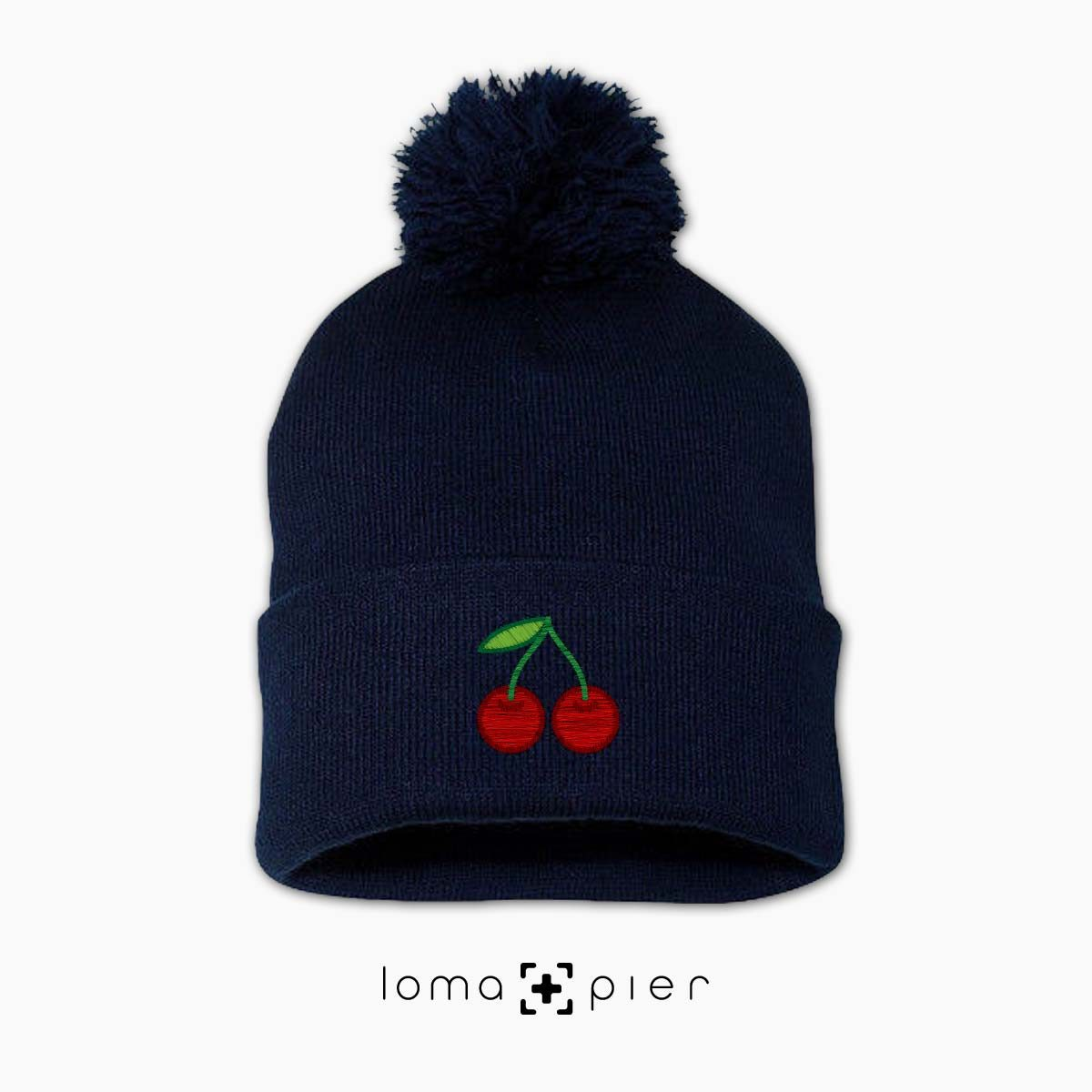 CHERRIES icon embroidered on a navy pom pom beanie by loma+pier beanie store