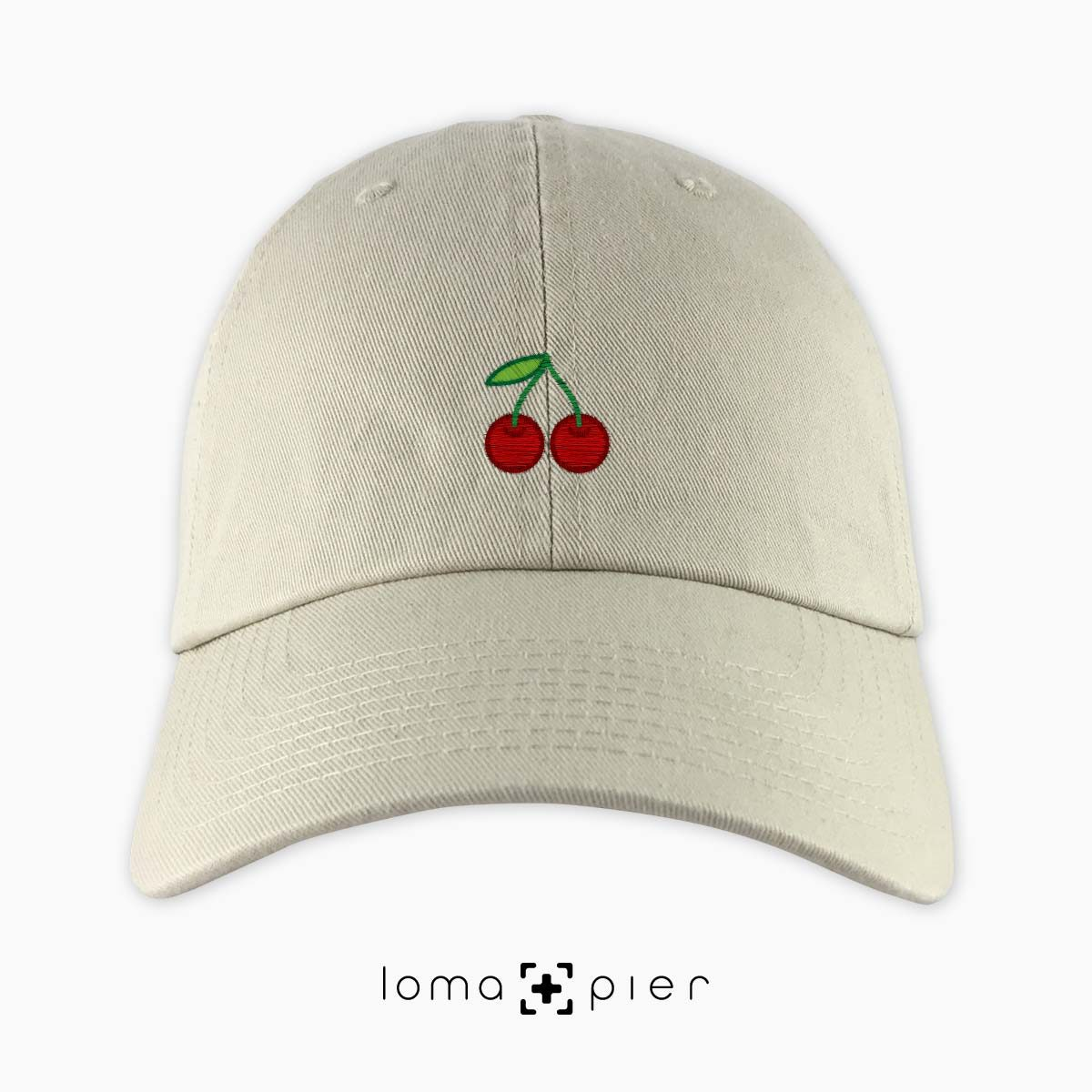 CHERRIES icon embroidered on a khaki dad hat by loma+pier hat store made in the USA