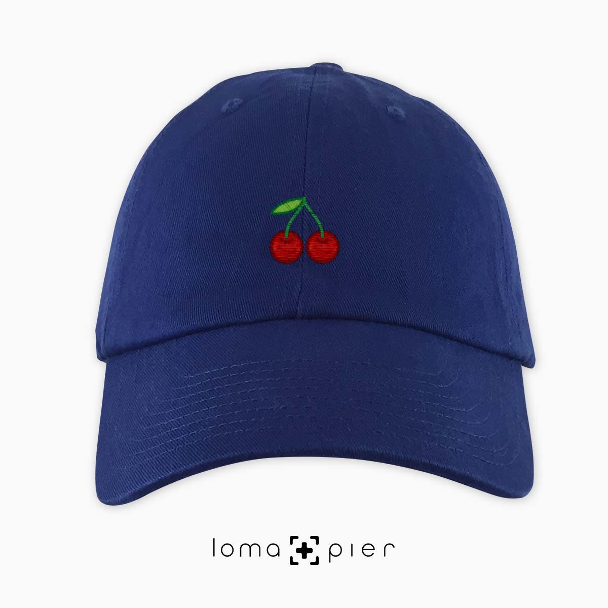 CHERRIES icon embroidered on a royal blue dad hat by loma+pier hat store made in the USA