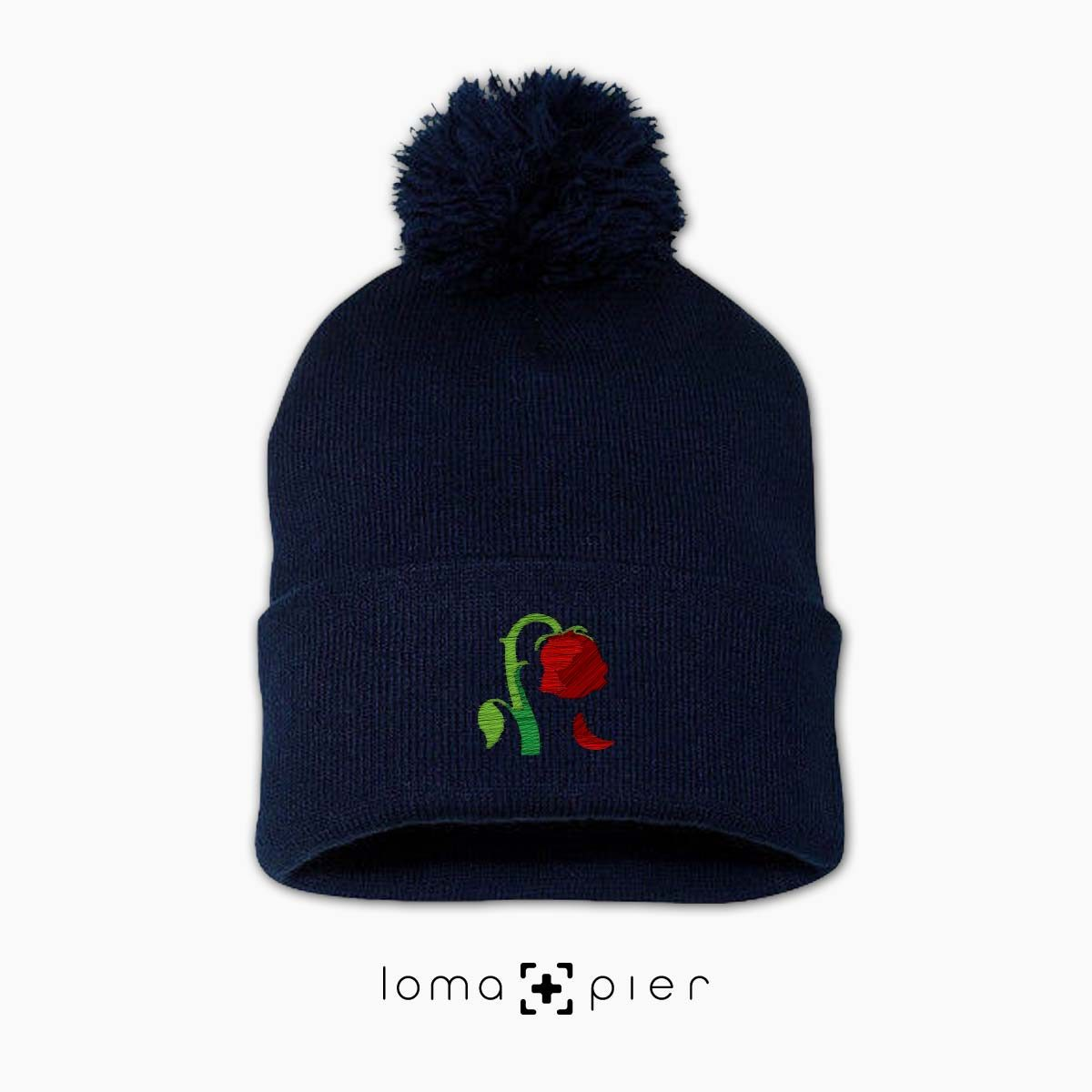 DYING ROSE EMOJI icon embroidered on a navy blue pom pom beanie by loma+pier hat store