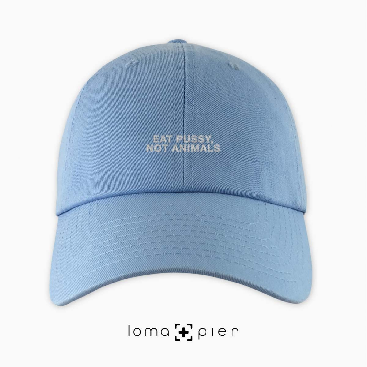 EAT PUSSY, NOT ANIMALS typography embroidered on a baby blue unstructured dad hat with white thread by loma+pier hat store made in the USA