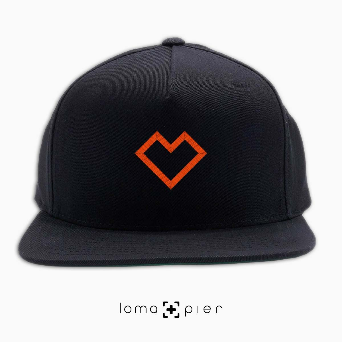 EDGY HEART icon embroidered on a black classic snapback hat with orange thread by loma+pier hat store