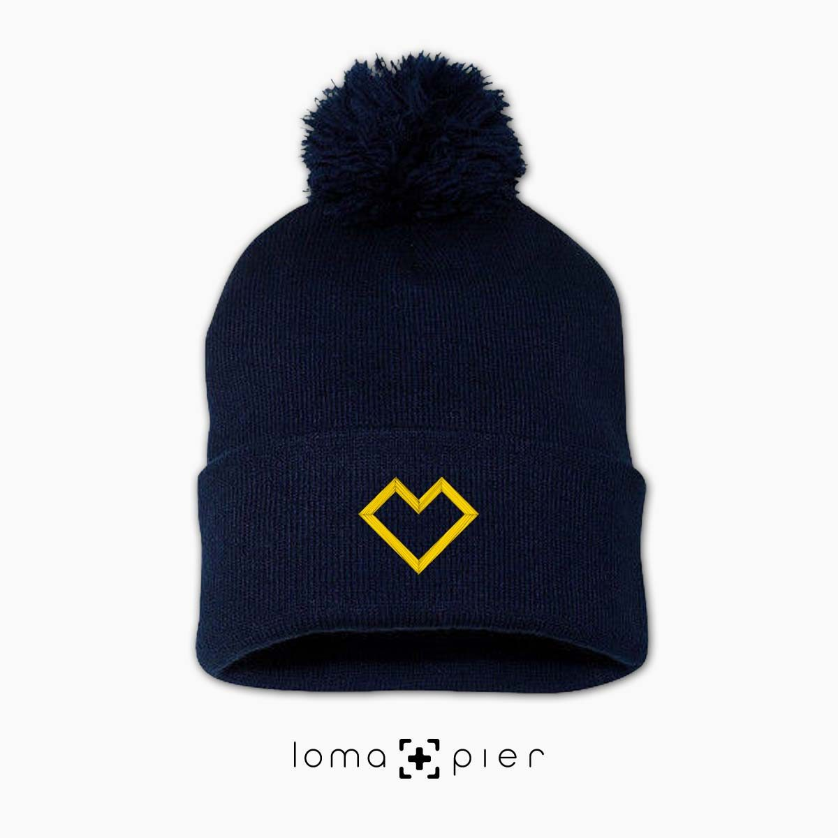 EDGY HEART icon embroidered on a navy blue pom pom beanie with yellow thread by loma+pier hat store
