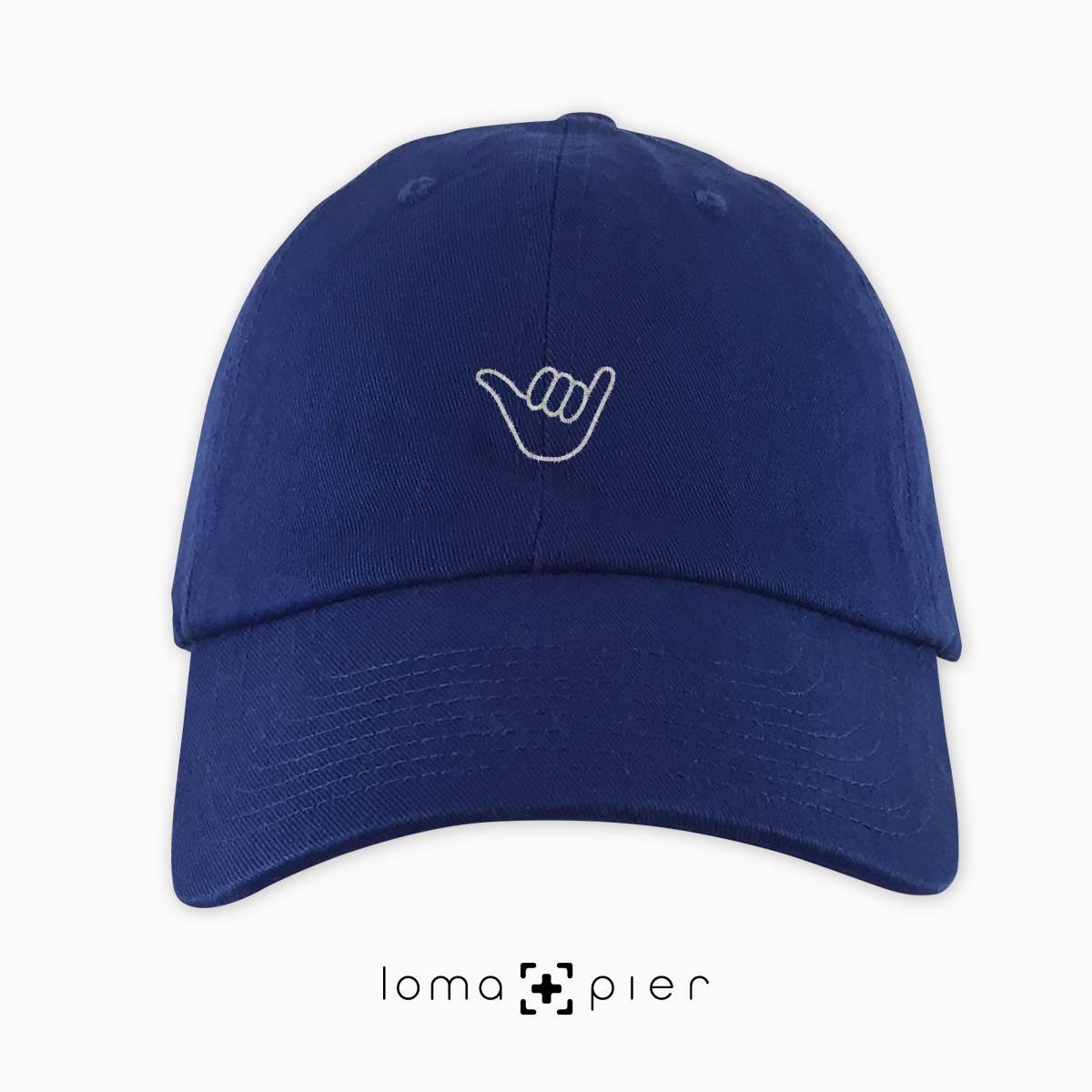HANG LOOSE icon embroidered on a royal blue unstructured dad hat by loma+pier hat store made in the USA