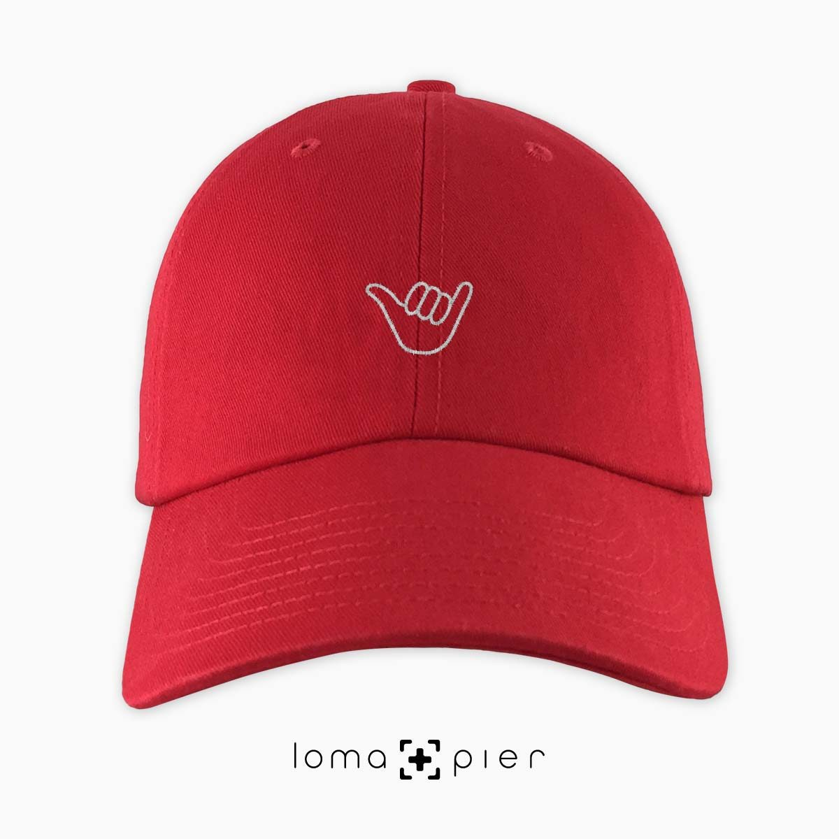HANG LOOSE icon embroidered on a red unstructured dad hat by loma+pier hat store made in the USA