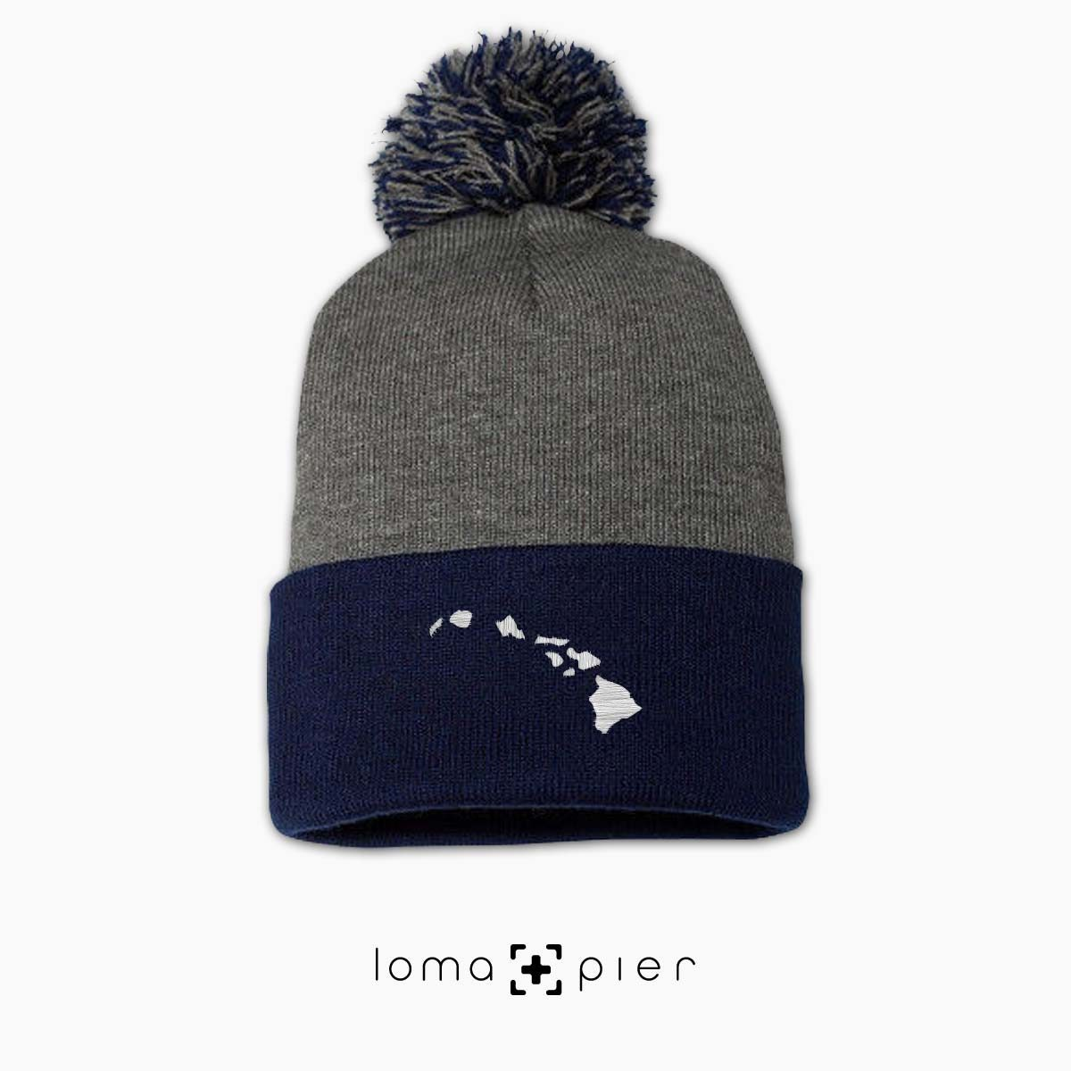 HAWAIIAN ISLANDS icon embroidered on a grey blue pom pom hawaii beanie by loma+pier hat store