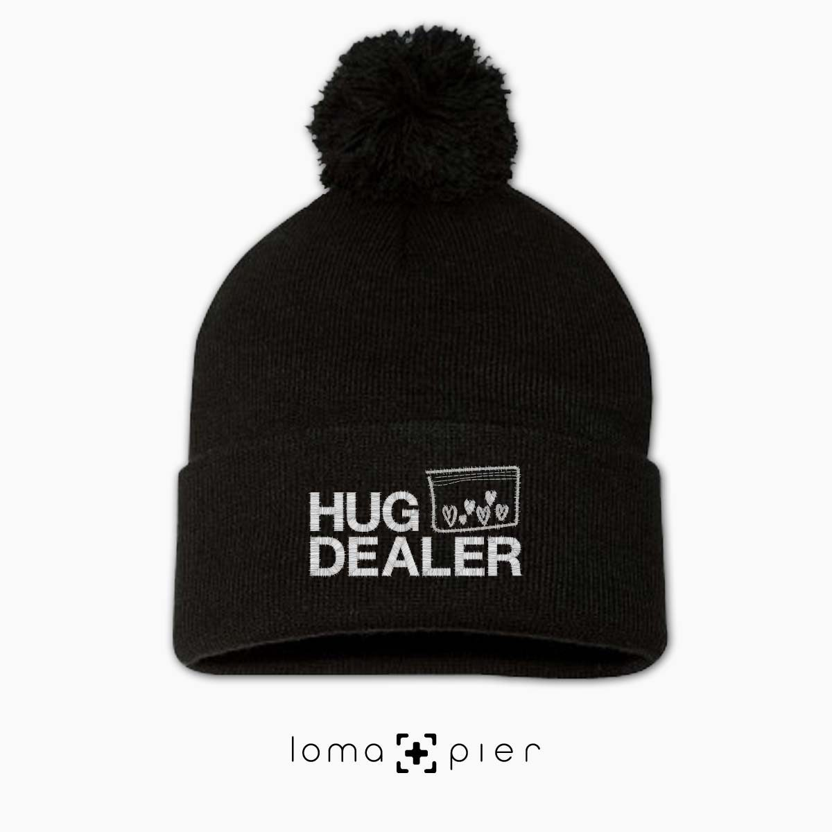 HUG DEALER icon embroidered on a black pom pom beanie with white thread by loma+pier hat store