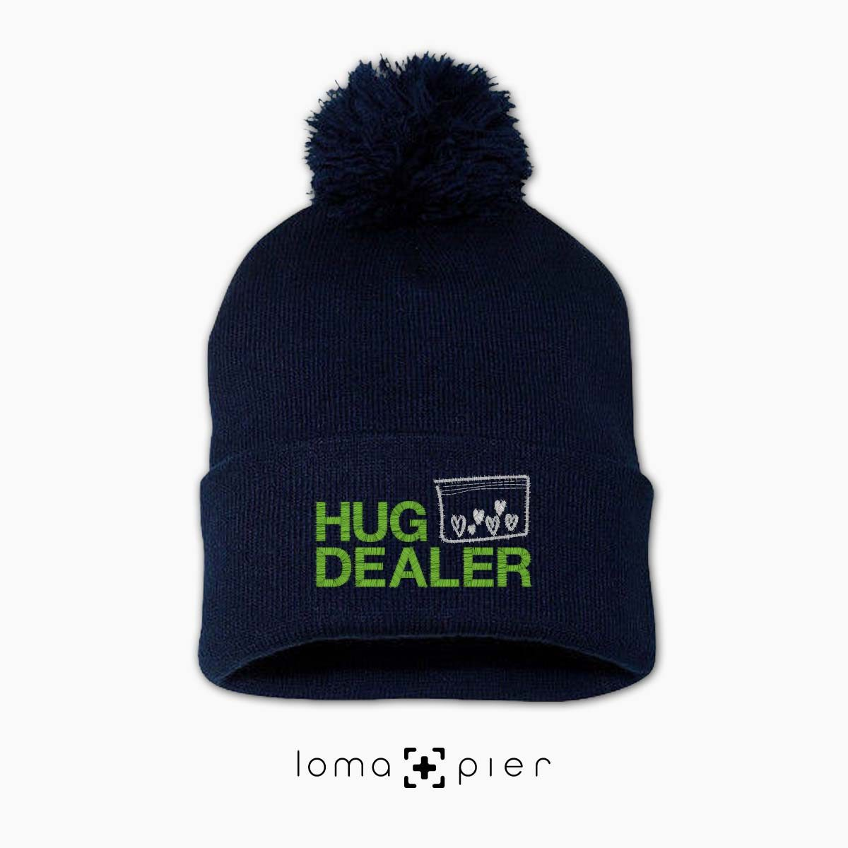 HUG DEALER icon embroidered on a navy blue pom pom beanie with multicolor thread by loma+pier hat store