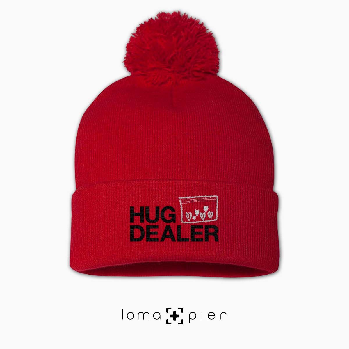 HUG DEALER icon embroidered on a red pom pom beanie with multicolor thread by loma+pier hat store