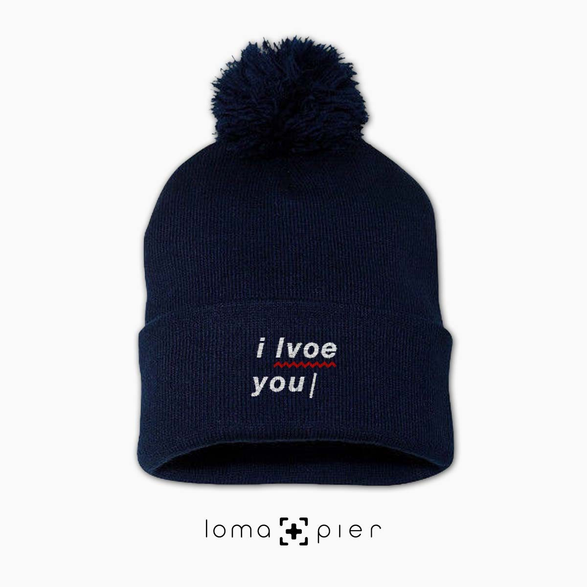 I LVOE YOU typography embroidered on a navy blue pom pom beanie with white thread by loma+pier hat store