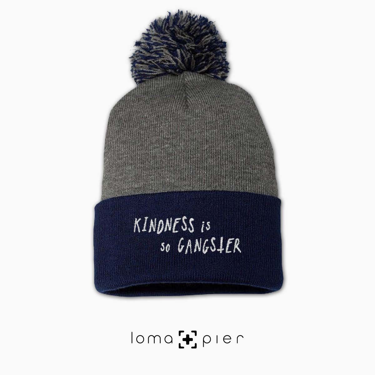 KINDNESS IS SO GANGSTER typography embroidered on a heather grey and navy blue pom pom beanie with white thread by loma+pier hat store