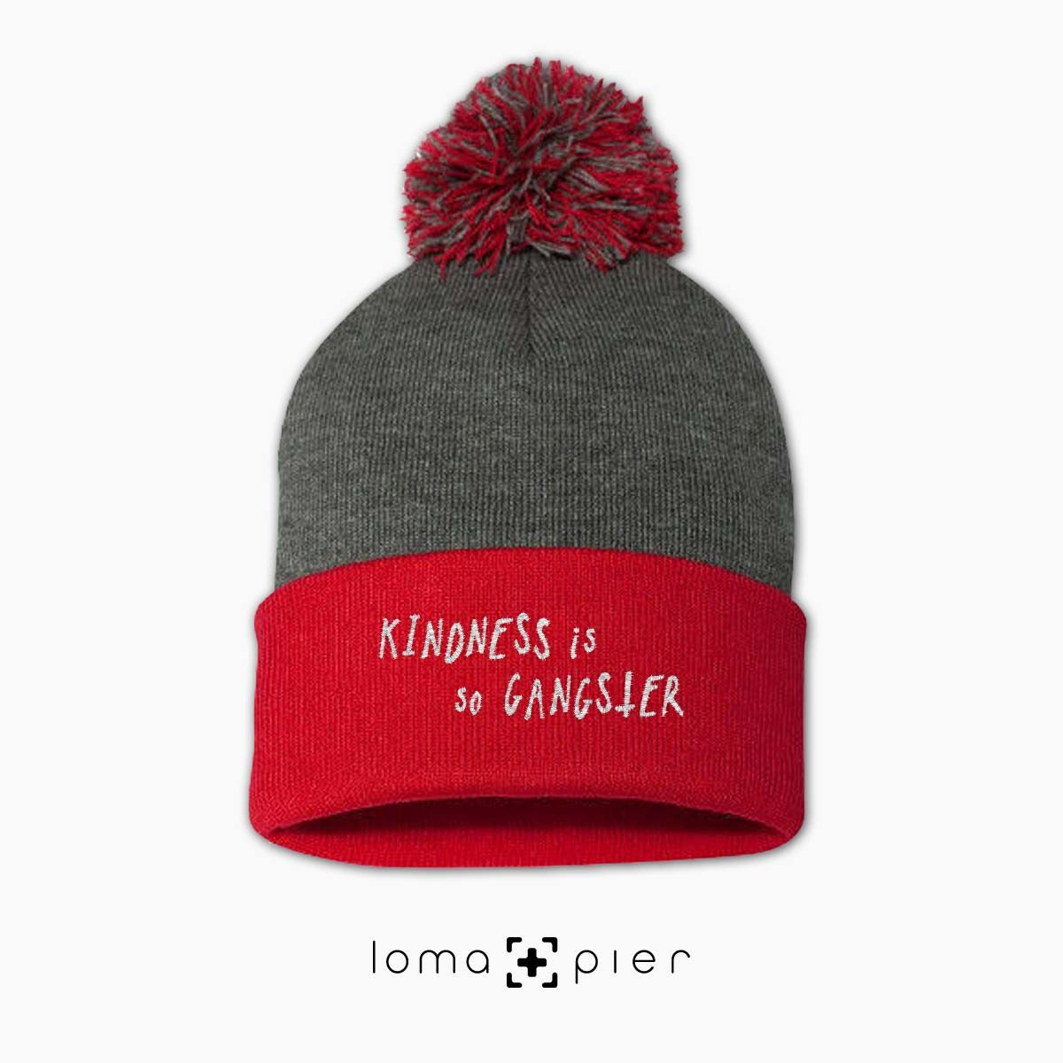 KINDNESS IS SO GANGSTER typography embroidered on a heather grey and red pom pom beanie with white thread by loma+pier hat store