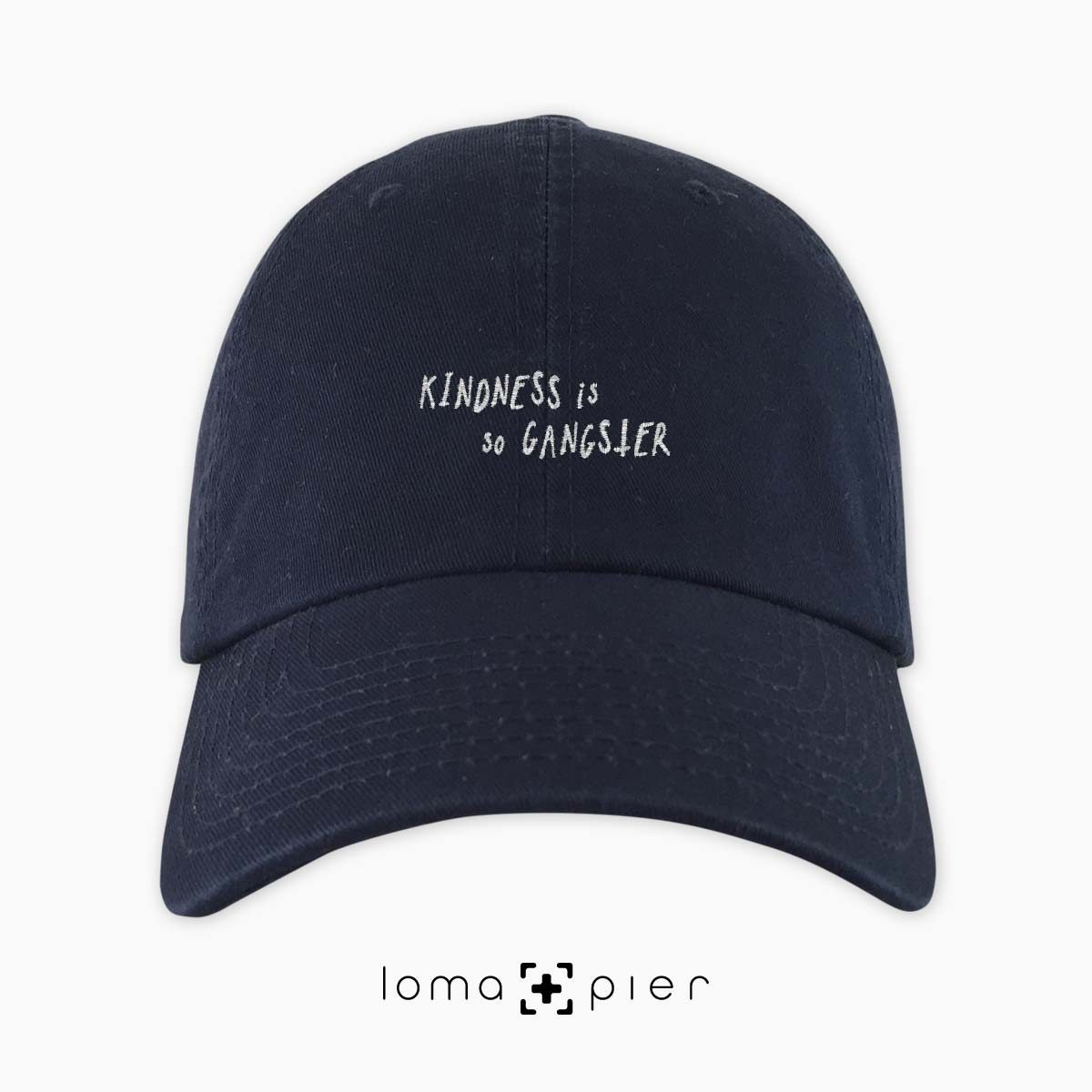 KINDNESS IS SO GANGSTER typography embroidered on a navy blue unstructured dad hat with white thread by loma+pier hat store made in the USA