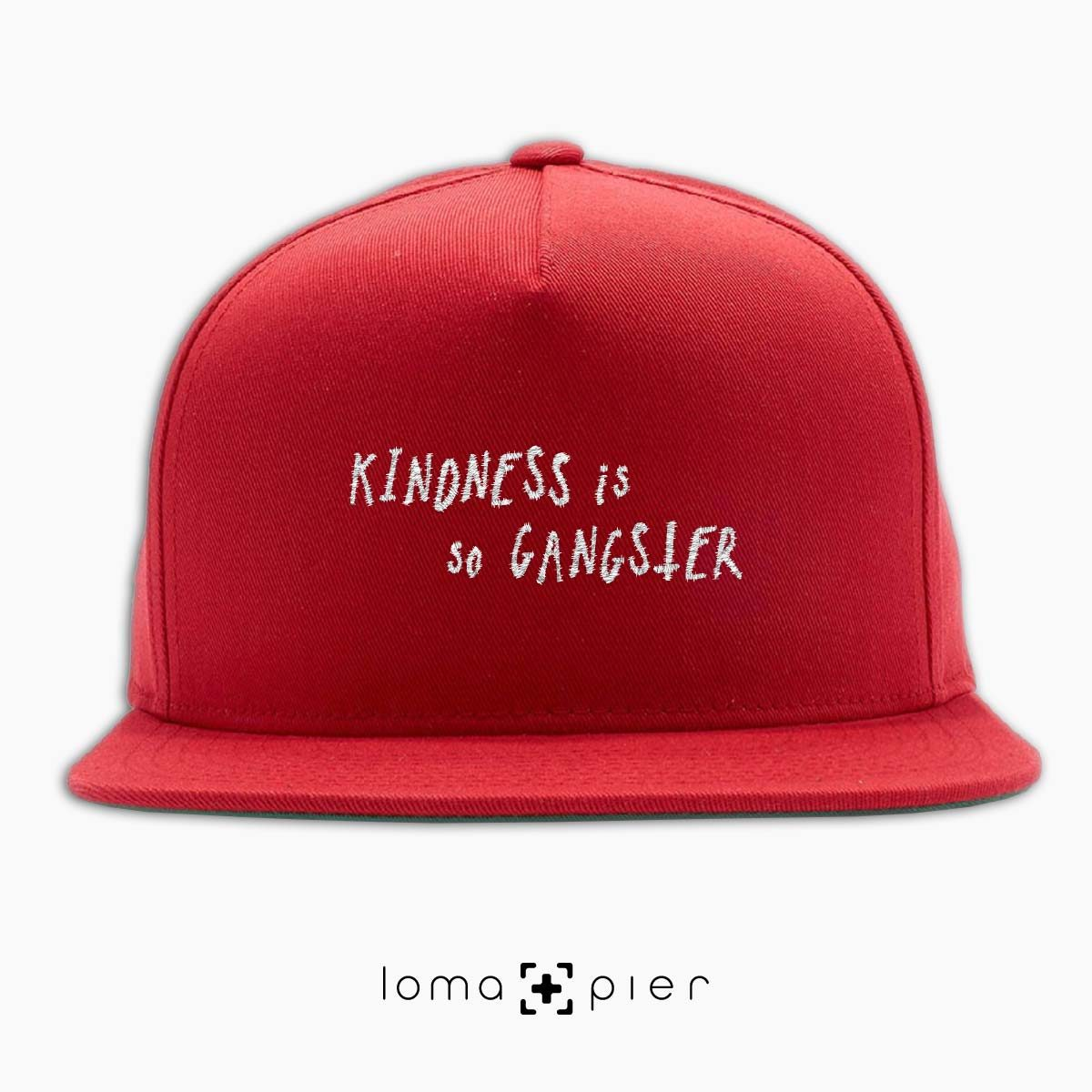 KINDNESS IS SO GANGSTER typography embroidered on a red classic snapback hat with white thread by loma+pier hat store