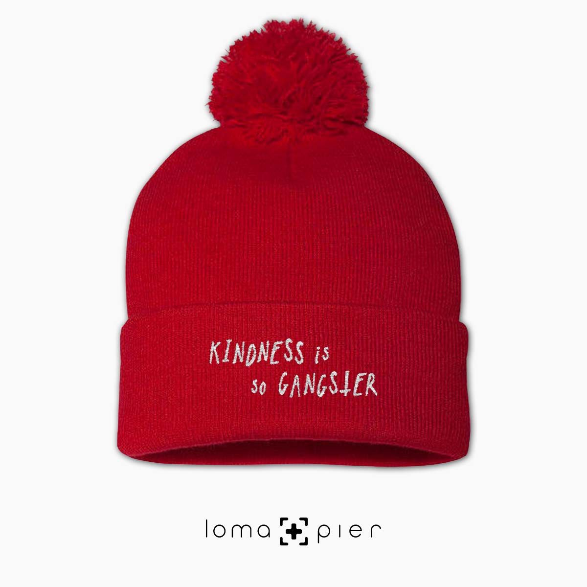 KINDNESS IS SO GANGSTER typography embroidered on a red pom pom beanie with white thread by loma+pier hat store