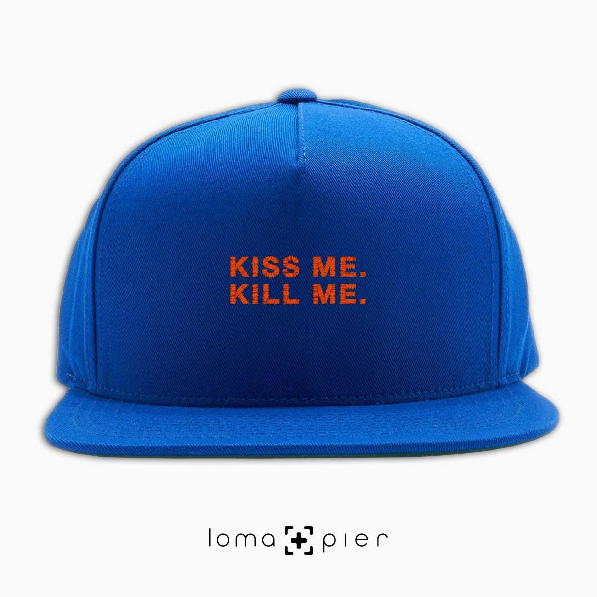 KISS ME. KILL ME. typography embroidered on a royal blue classic snapback hat with orange thread by loma+pier hat store