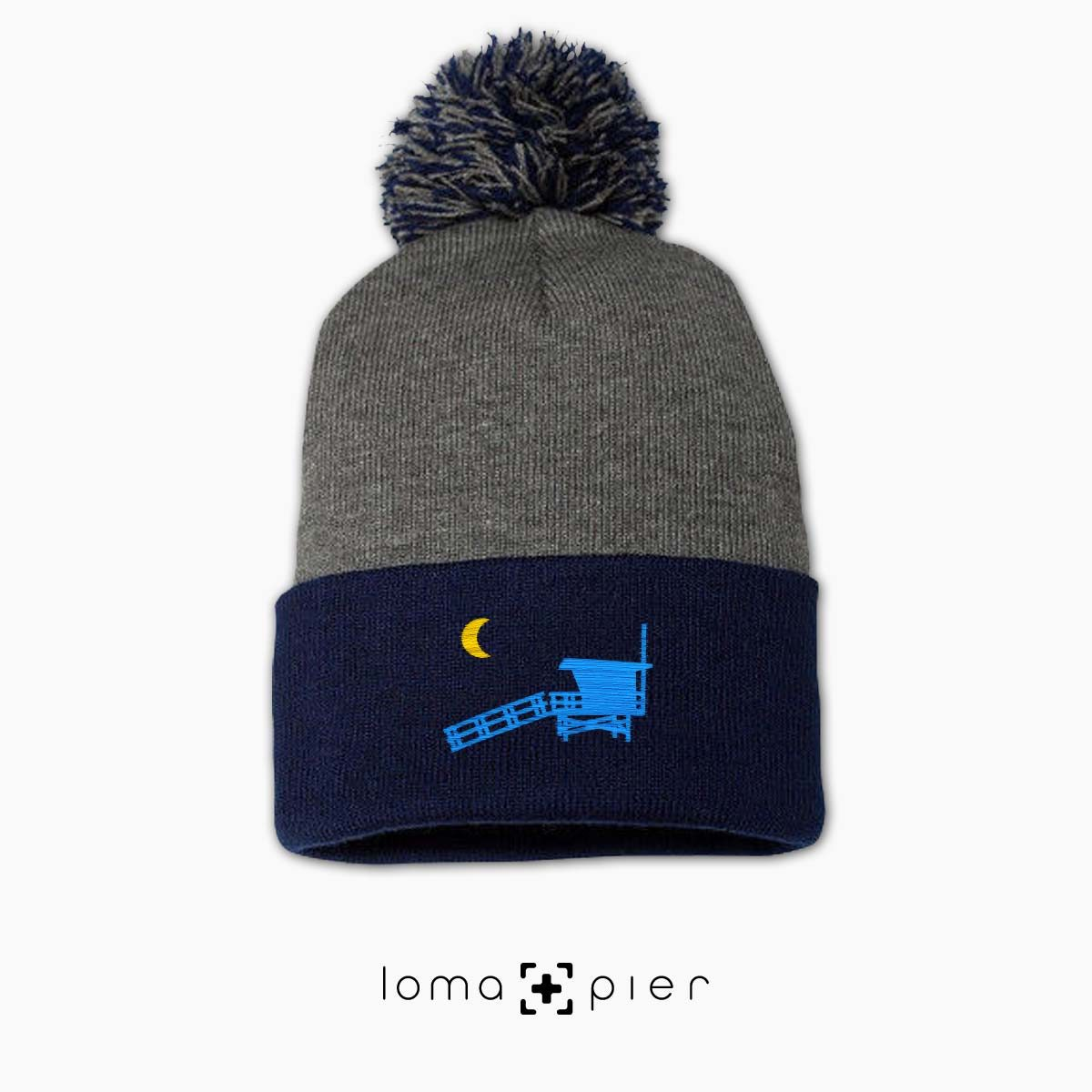 LIFEGUARD TOWER icon embroidered on a navy grey pom pom beanie by loma+pier hat store