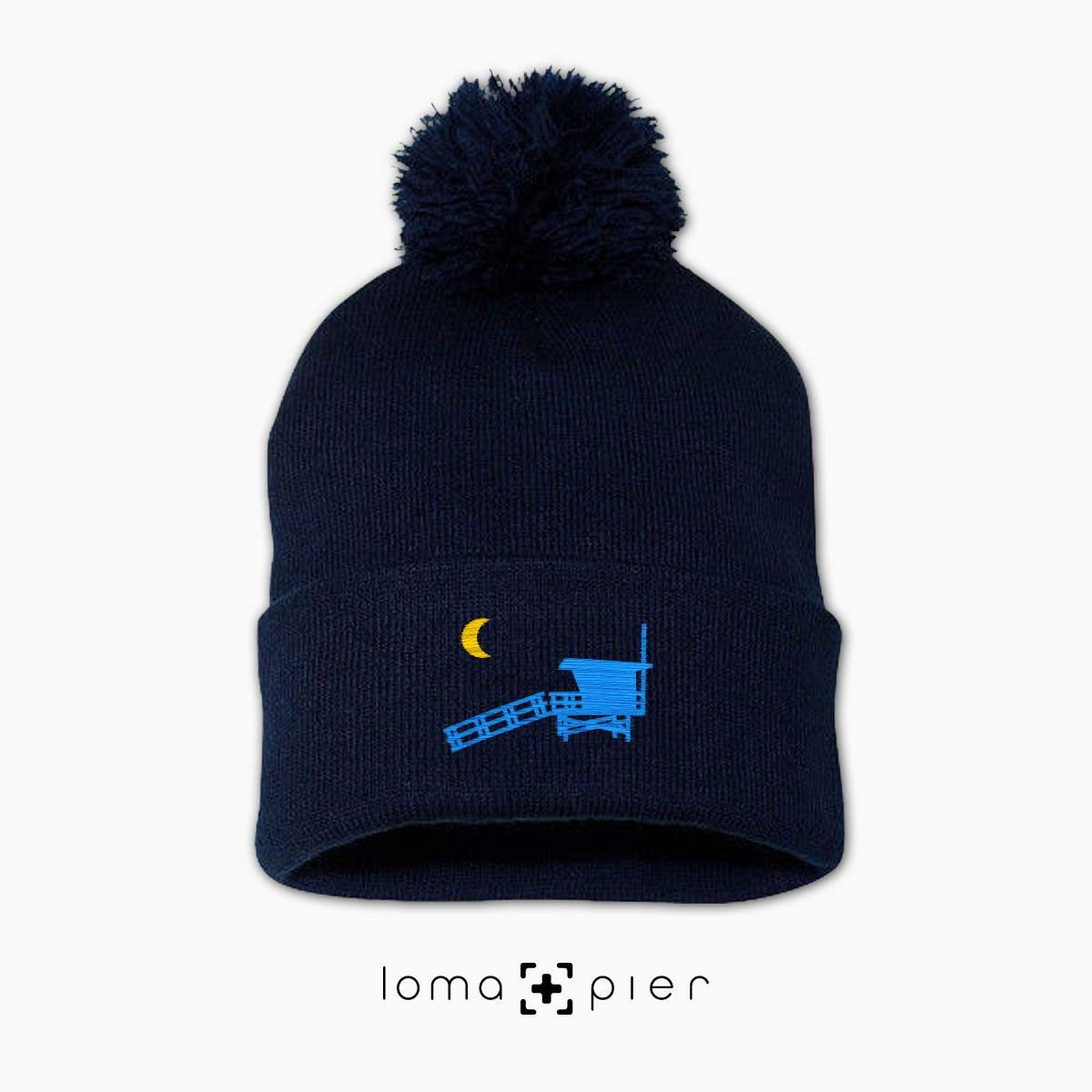 LIFEGUARD TOWER icon embroidered on a navy pom pom beanie by loma+pier hat store