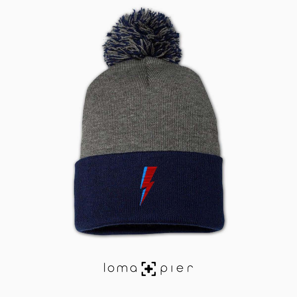 LIGHTNING BOLT icon embroidered on a heather grey and navy blue pom pom beanie with multicolor thread by loma+pier hat store