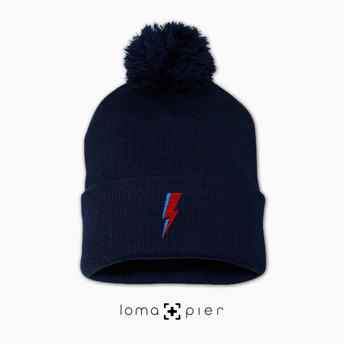 LIGHTNING BOLT icon embroidered on a navy blue pom pom beanie with multicolor thread by loma+pier hat store