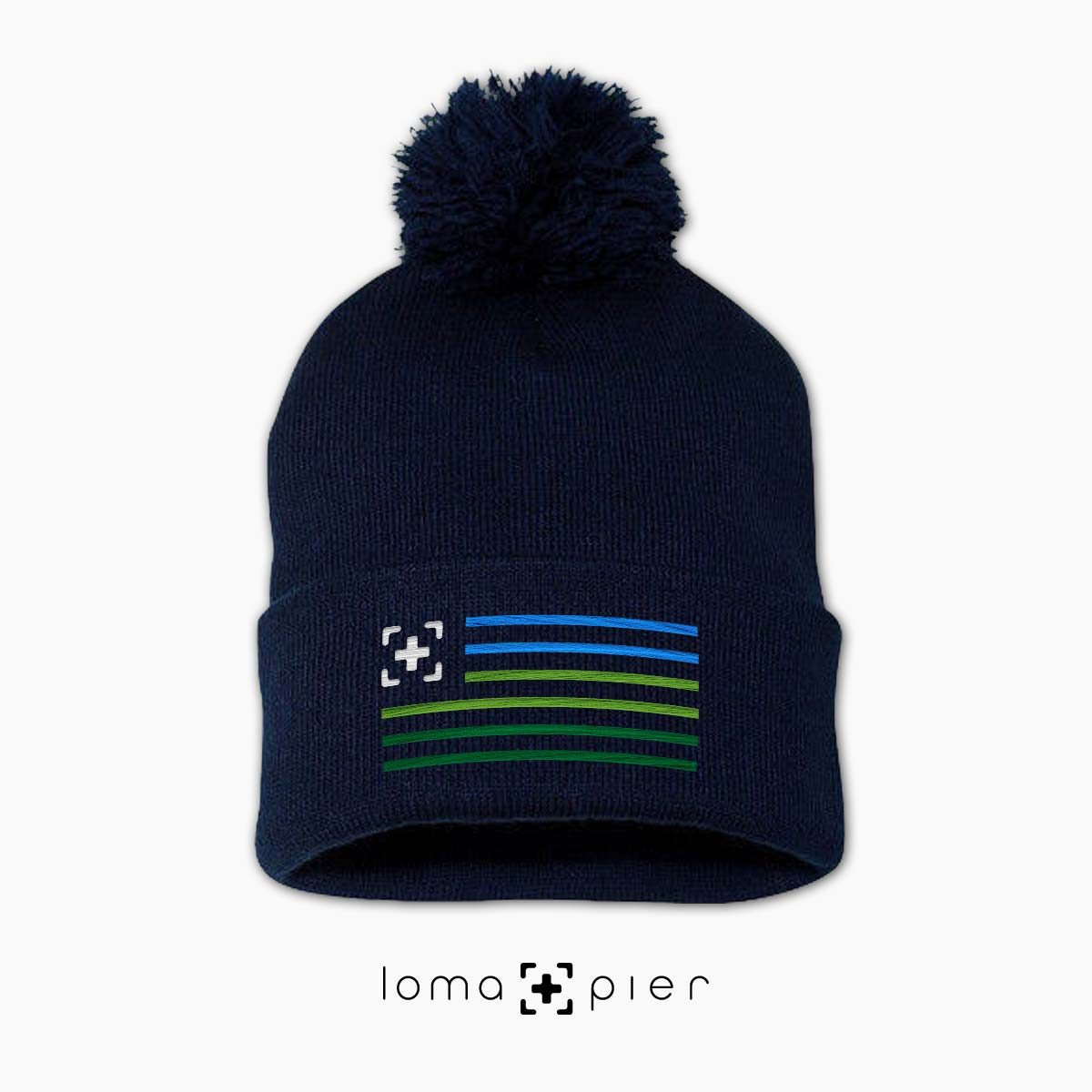 loma+stripes icon embroidered on a navy pom pom beanie by loma+pier beanie store