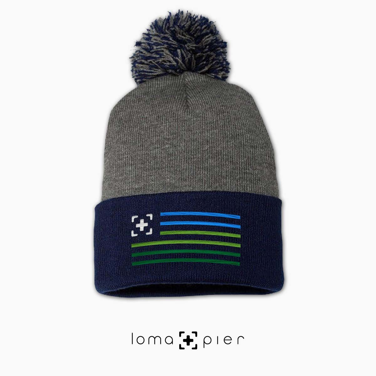 loma+stripes icon embroidered on a navy grey pom pom beanie by loma+pier beanie store
