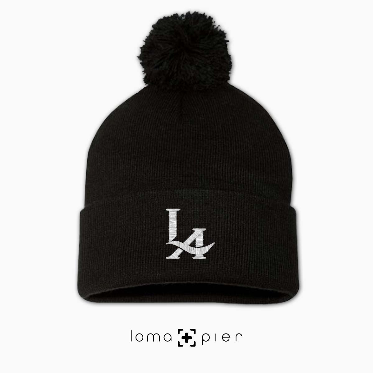 84bf4cb1977 los angeles LA LOGO icon embroidered on a black pom pom beanie by loma+pier