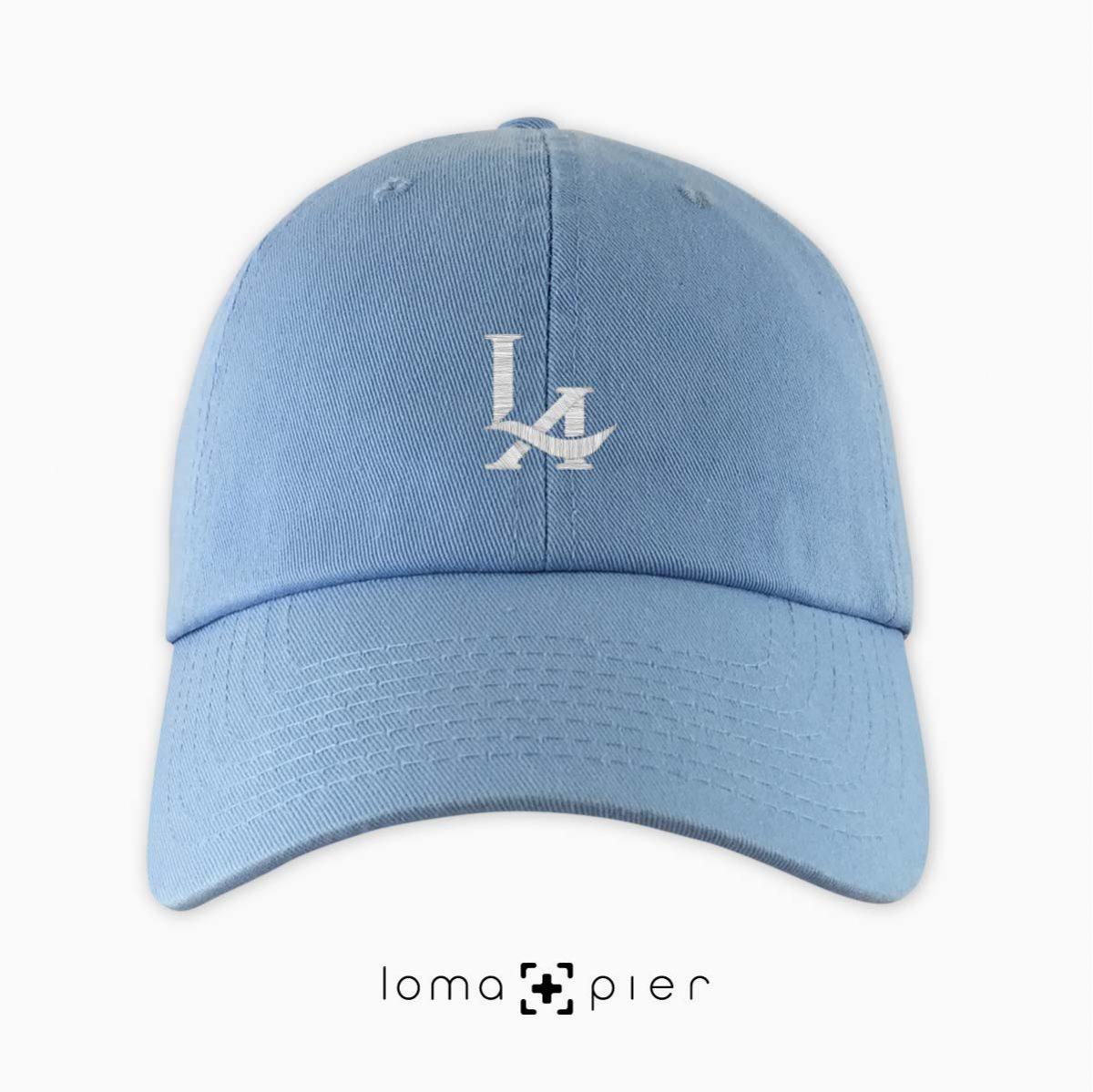 los angeles LA logo embroidered on a light blue unstructured dad hat by loma+pier hat store made in the USA