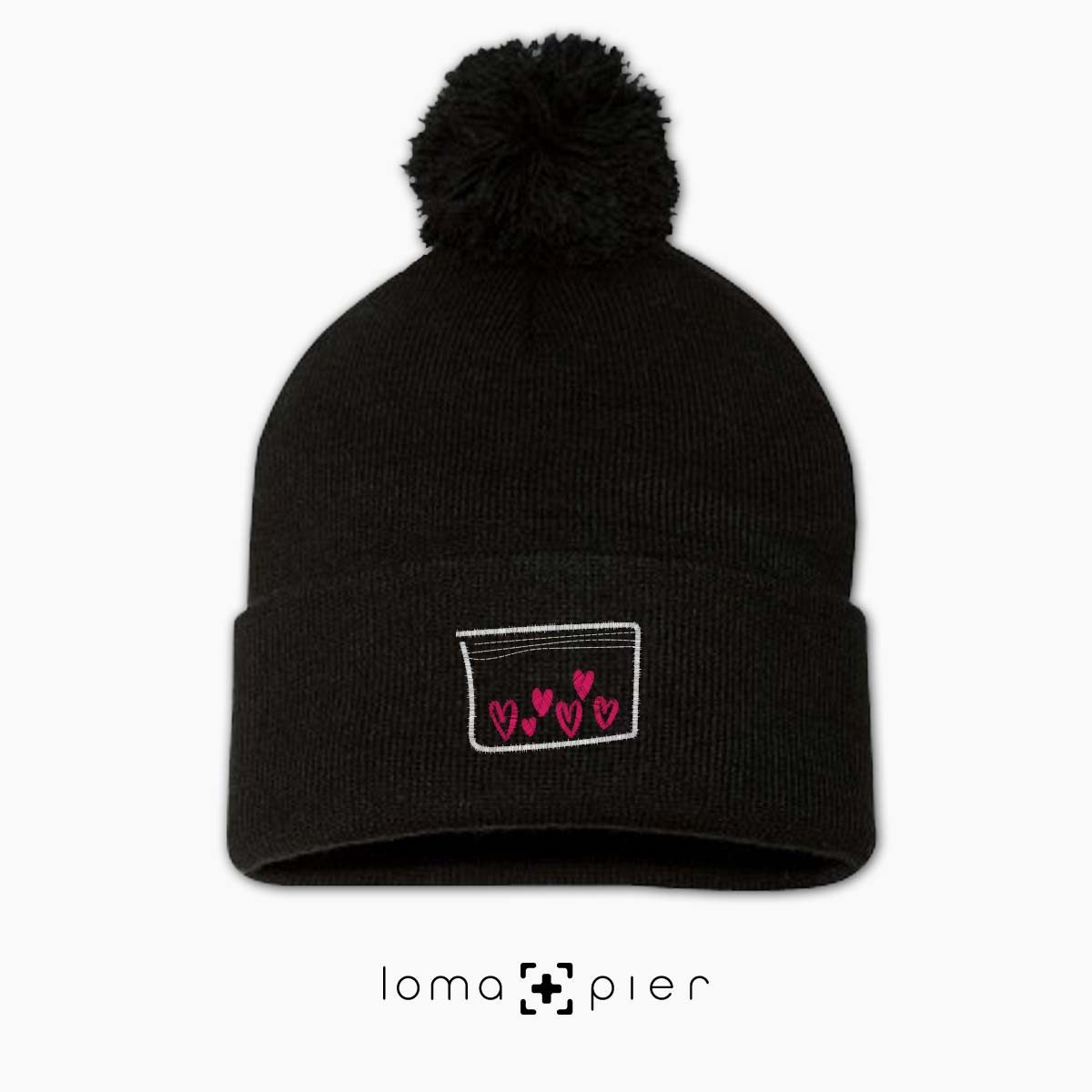 LOVE DRUG icon embroidered on a black pom pom beanie with pink thread by loma+pier hat store
