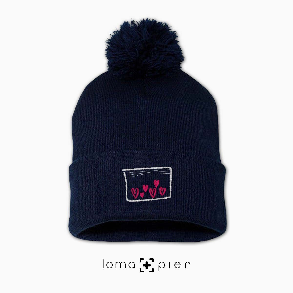 LOVE DRUG icon embroidered on a navy blue pom pom beanie with pink thread by loma+pier hat store