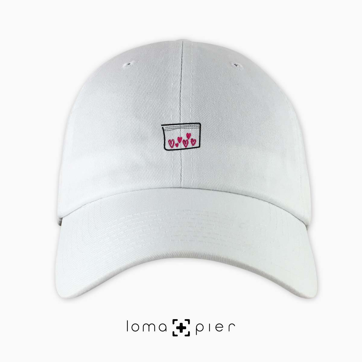 LOVE DRUG icon embroidered on a white unstructured dad hat with pink thread by loma+pier hat store made in the USA