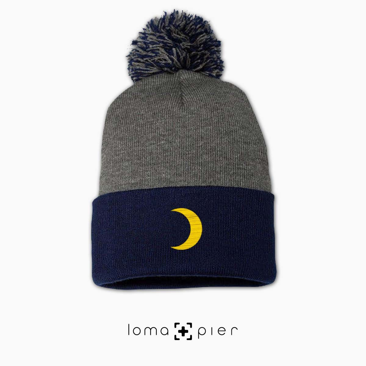 MOON icon embroidered on a grey navy pom pom beanie by loma+pier beanie store